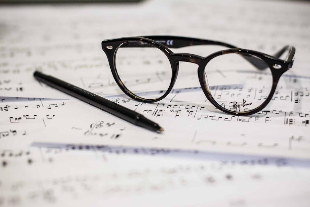black framed panto-style eyeglasses beside black ballpoint pen