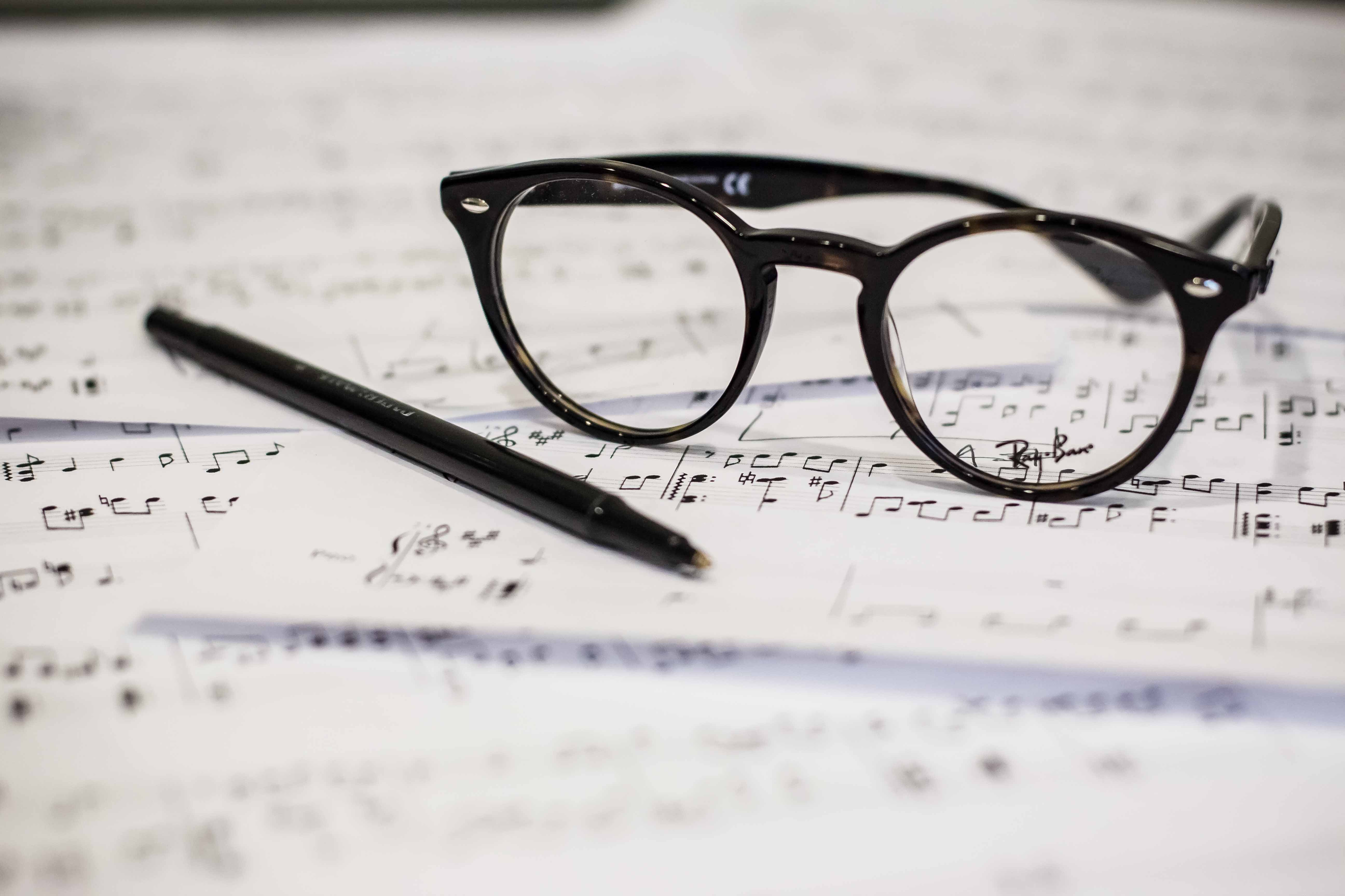 A pen and a pair of glasses on music sheets