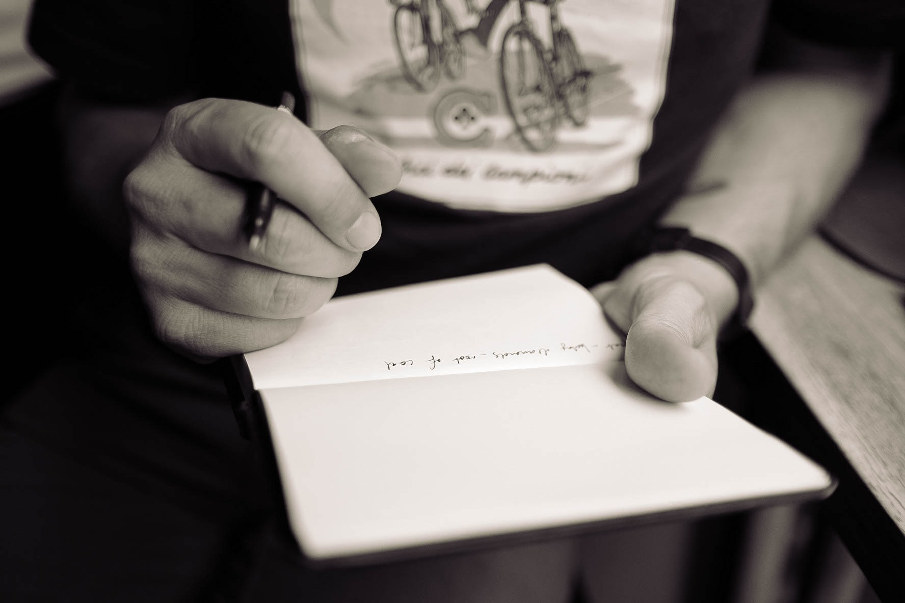 A desaturated shot of a person writing on a blank page