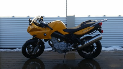 black and yellow bmw sports bike parked near white wall vehicle teams background