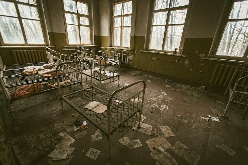صورة لغرفة مهجورة وبها اسرة صغيرة واوراق مبعثرة على الارض