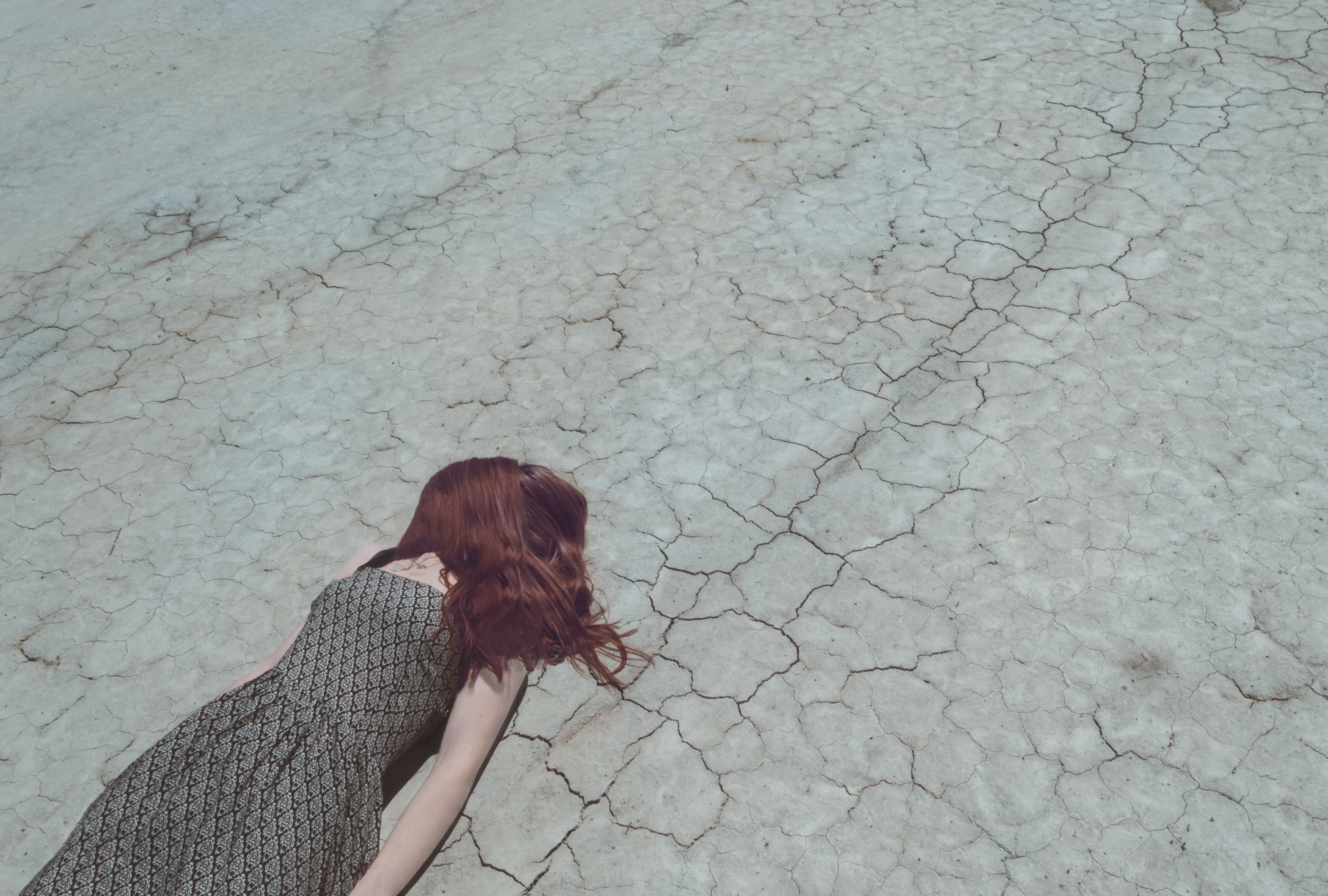Woman with hair over face lying down on cracked desert floor