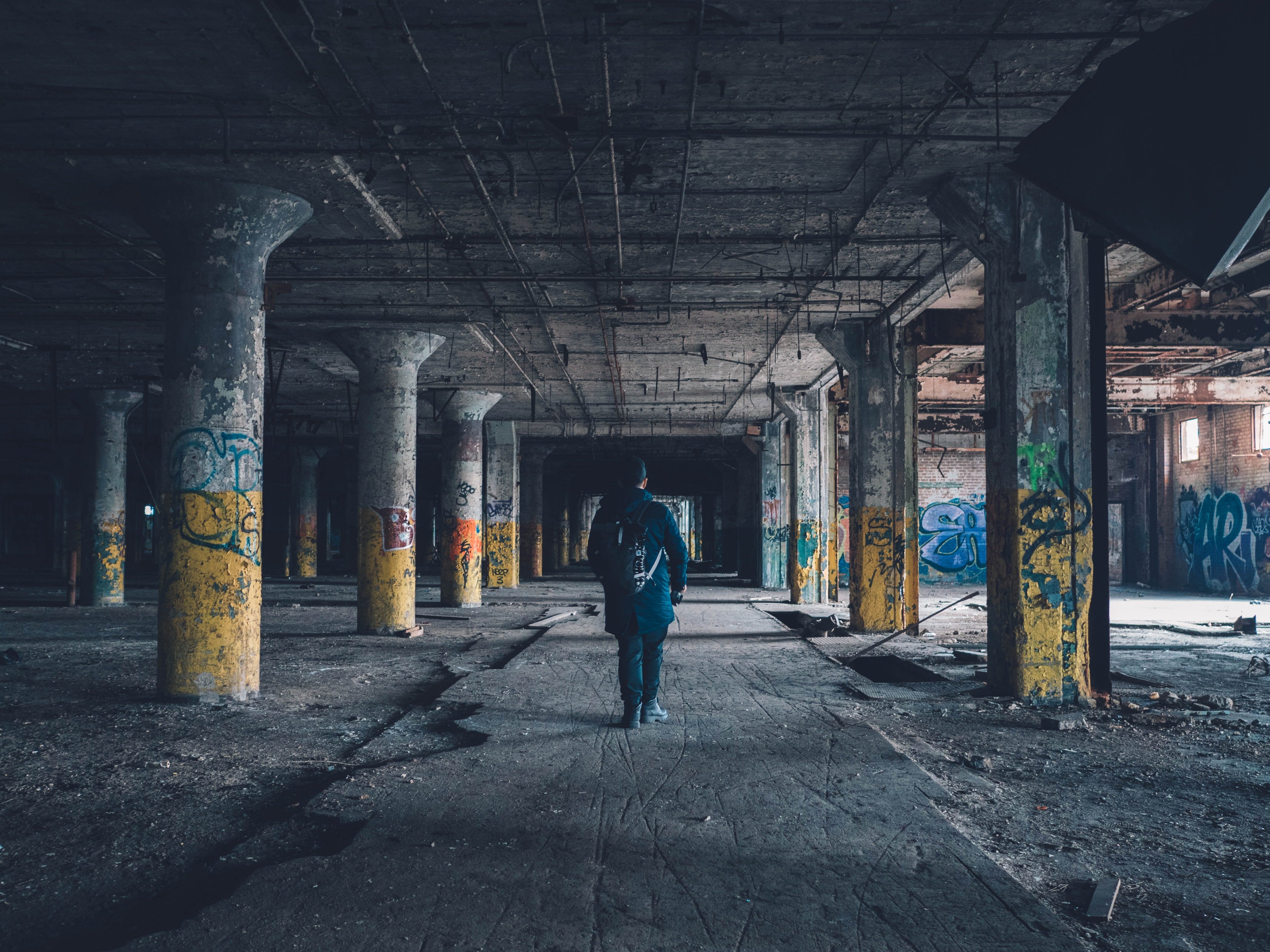 A man standing in an abandoned parking garage that's filled with graffiti in Detroit