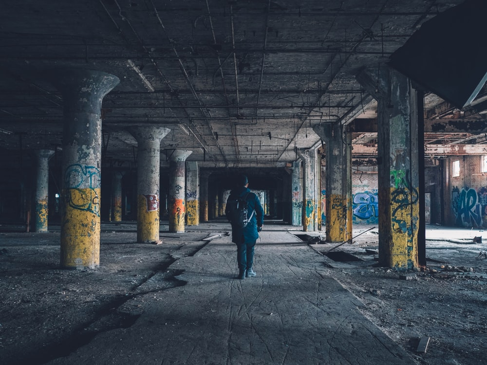 man walking hallway during daytime