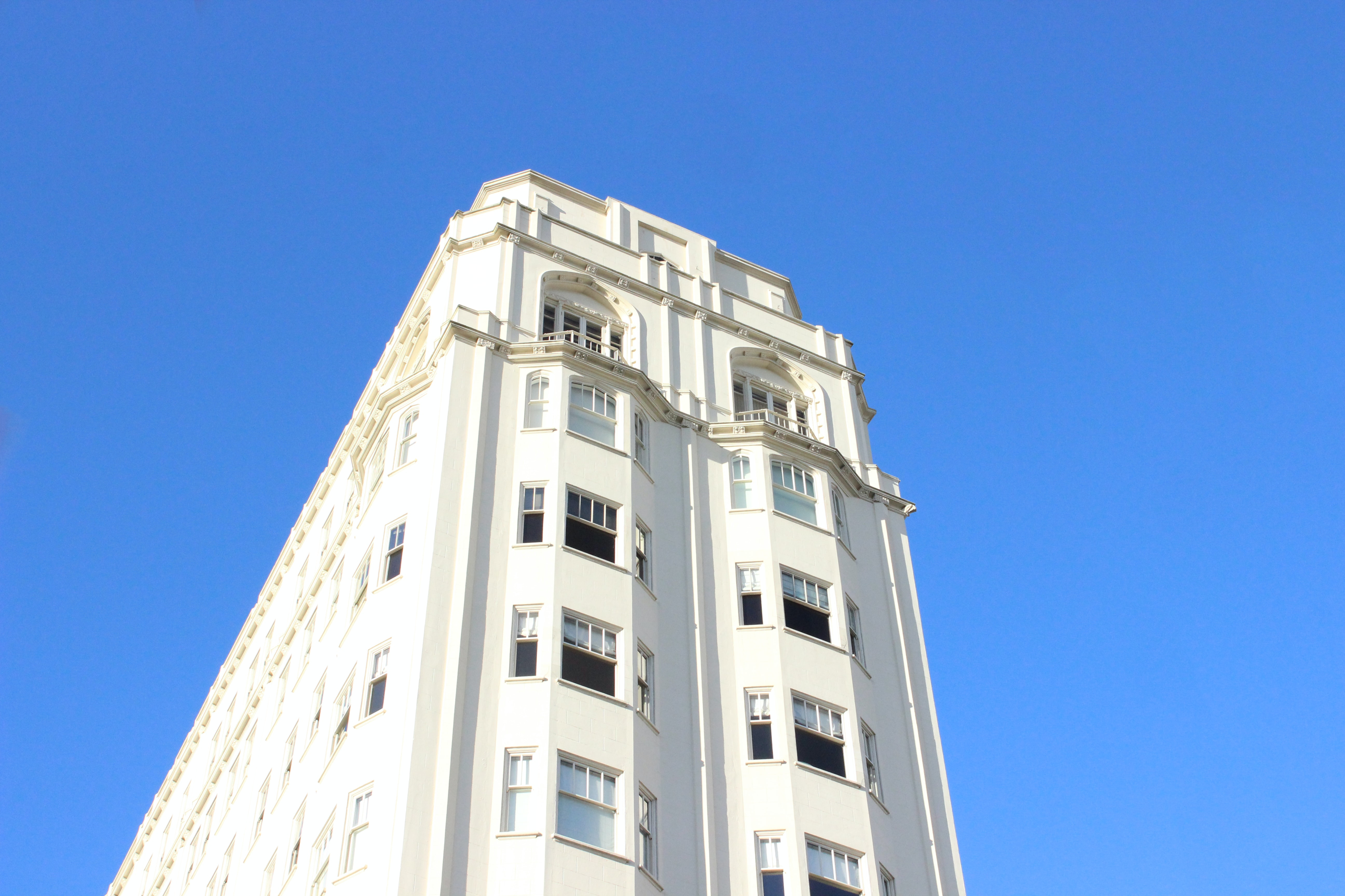 Looking skyward from an old white building in San Francisco.