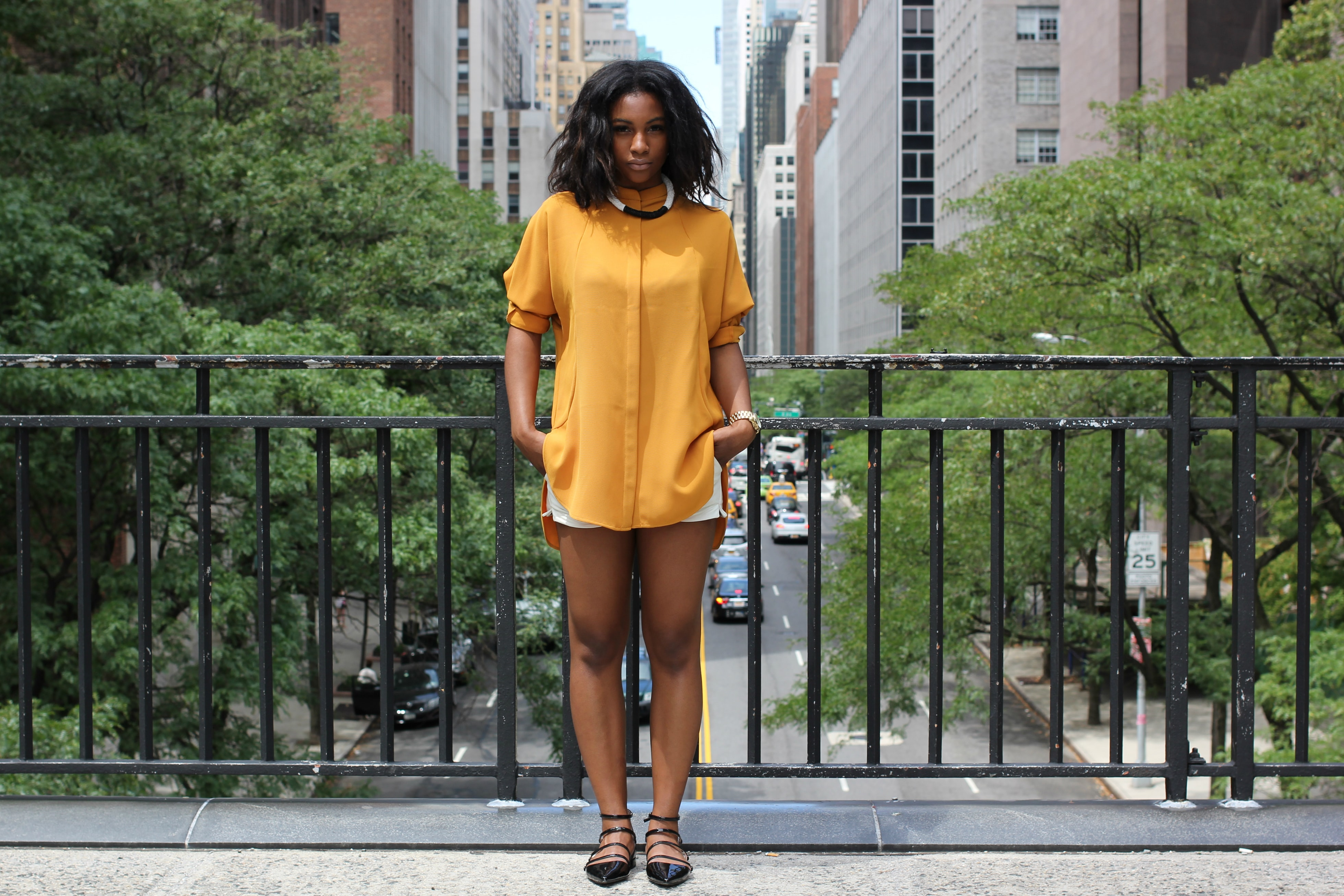 Woman models a yellow shirt and shorts on a bridge in New York