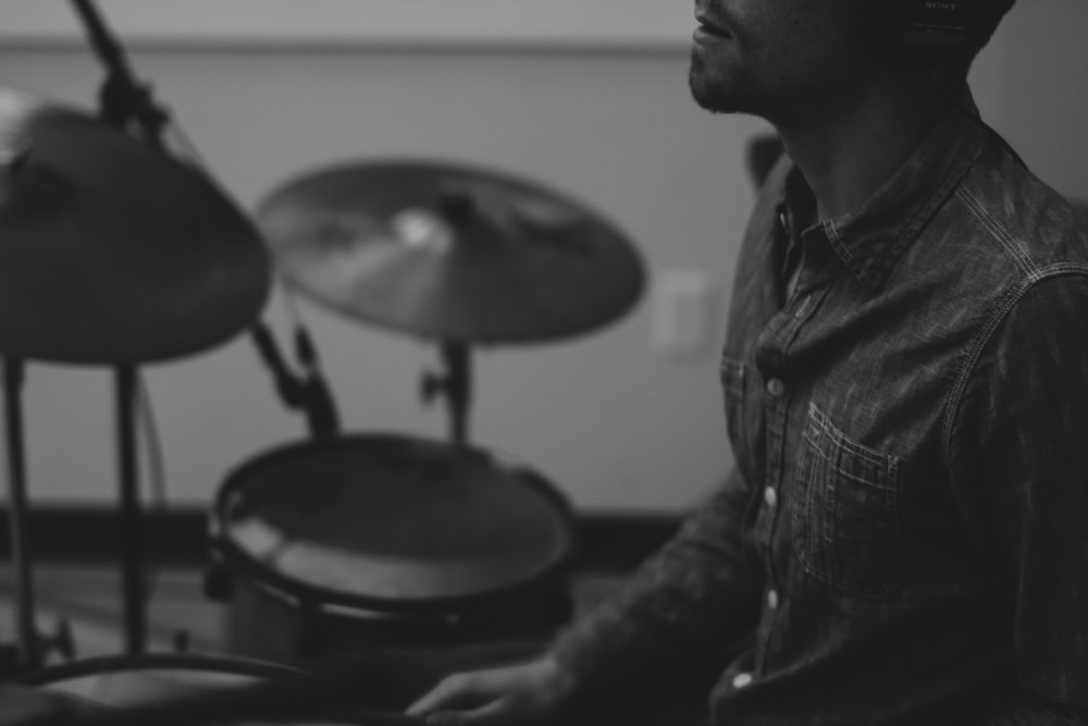 grayscale photo of man playing drum