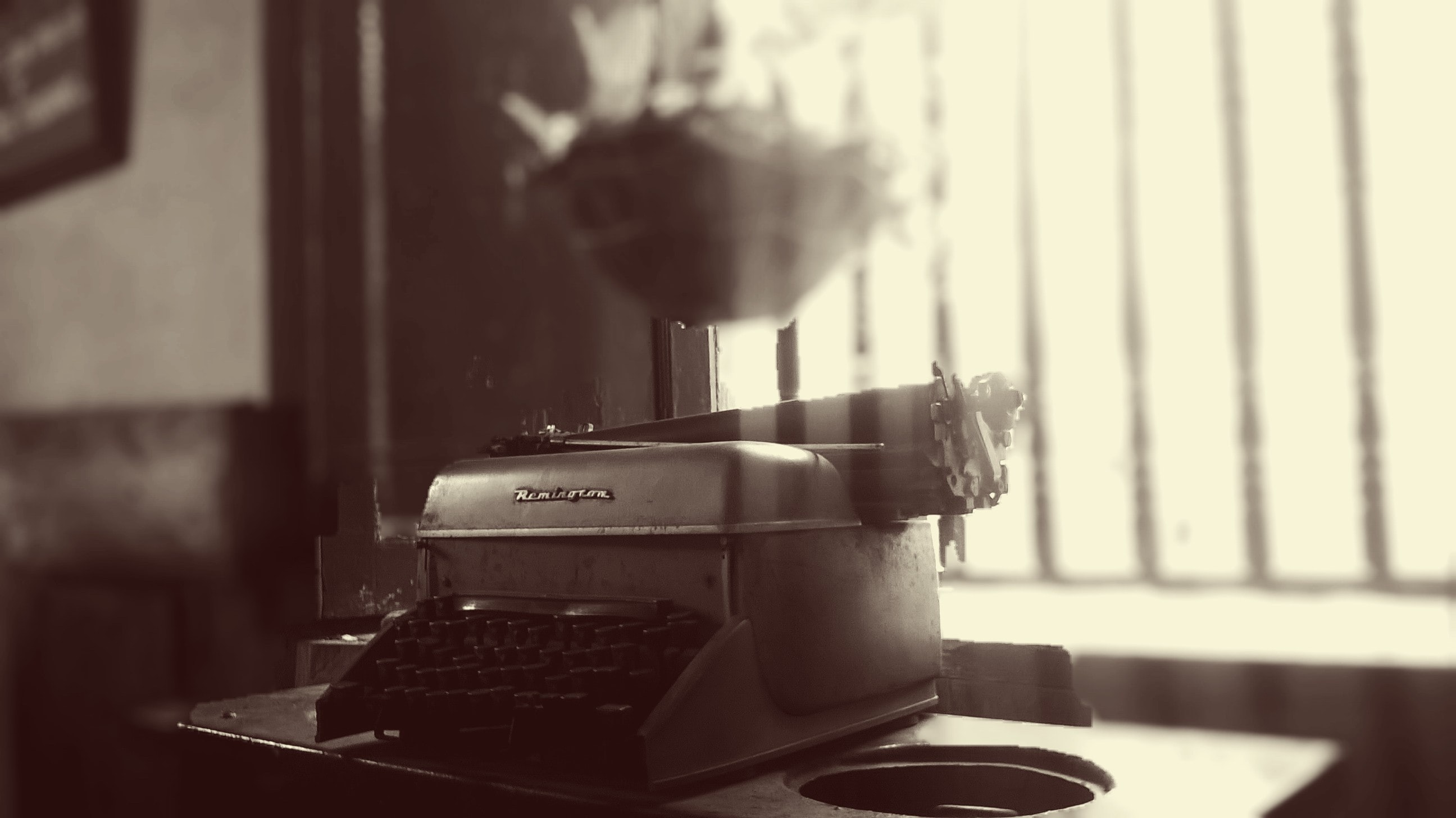 An old antique typewriter sits near a window with soft light coming through.