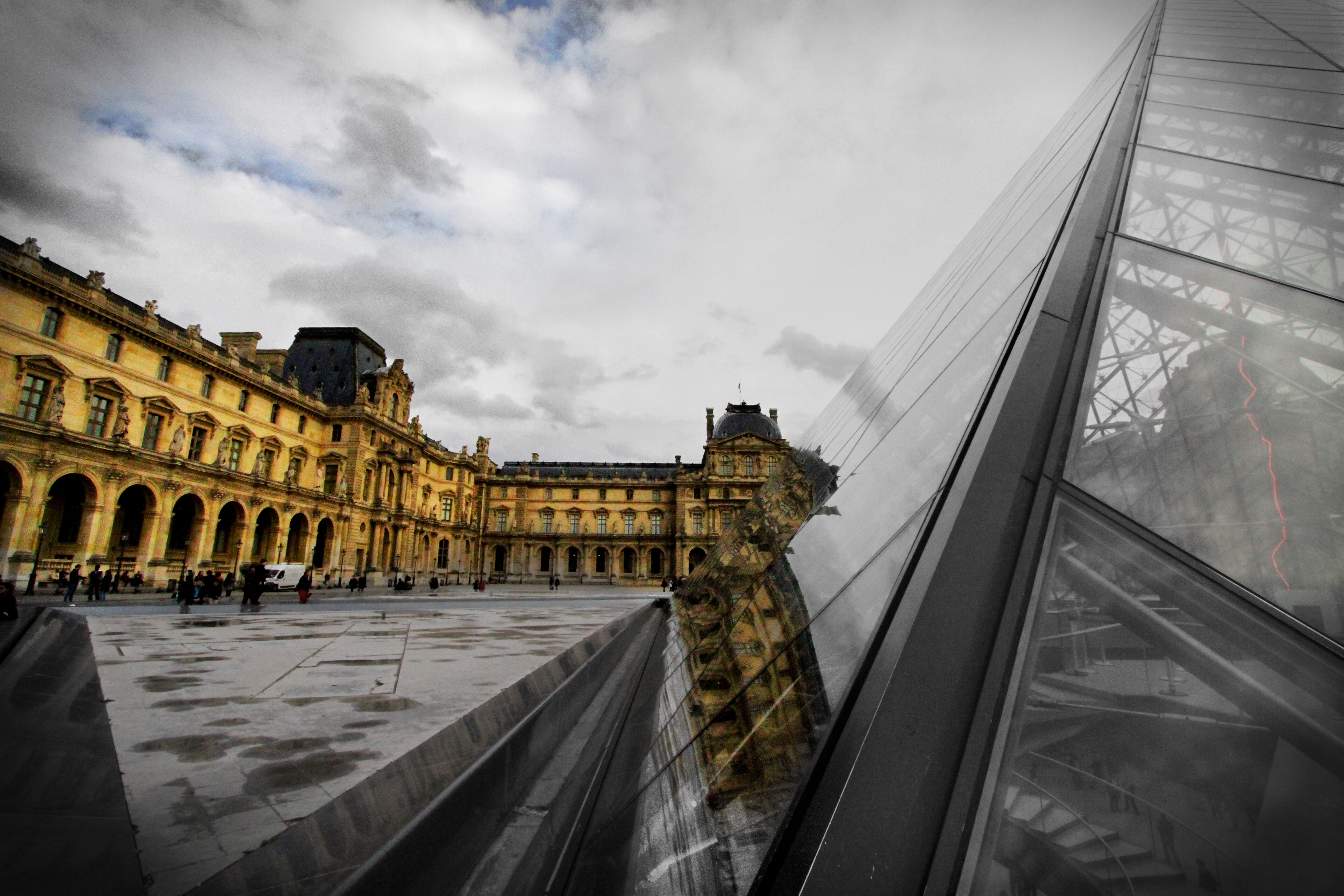 A glass window building, next to a large pavement walking in France.
