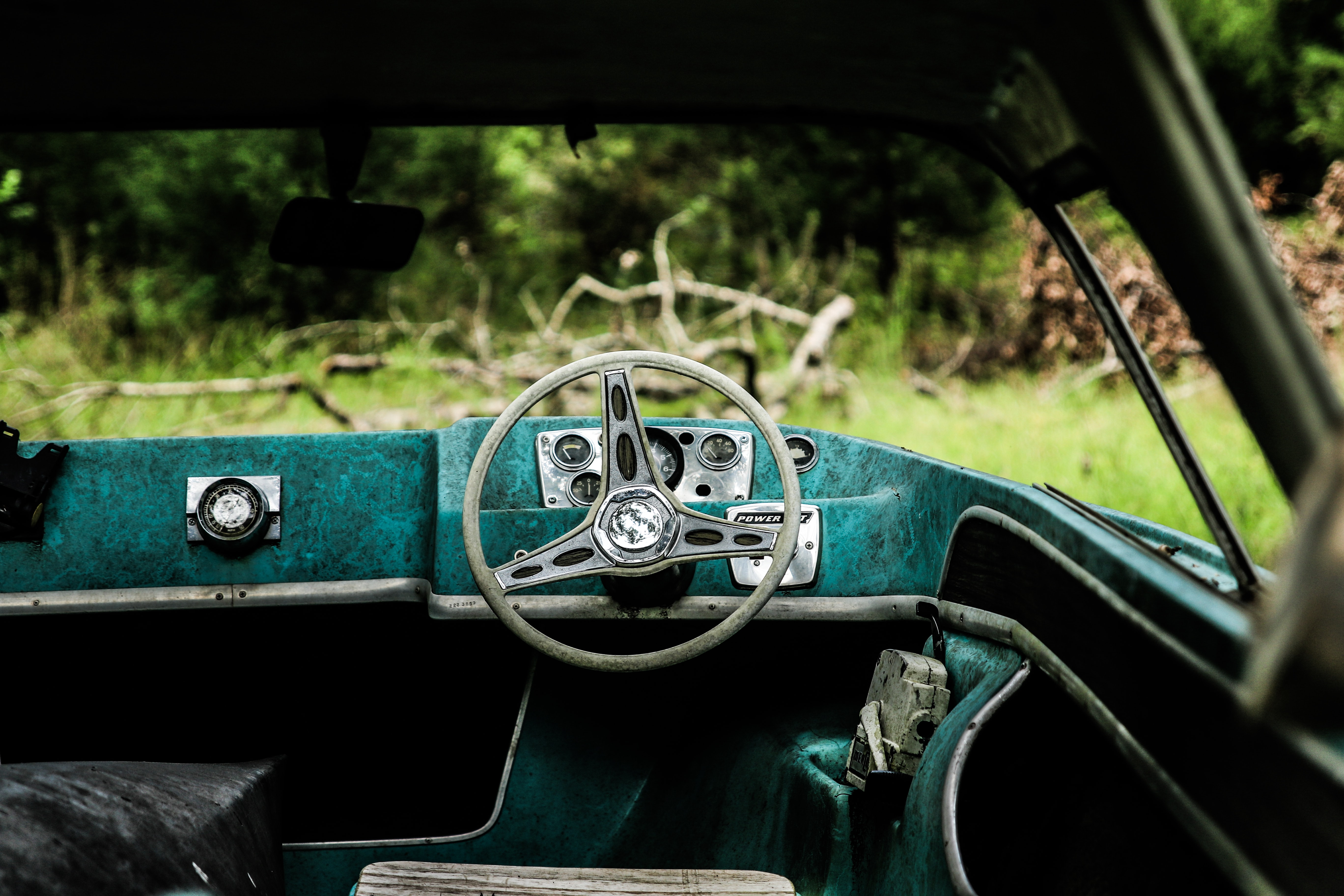 blue and black boat steering wheel interior near green grass field during daytime