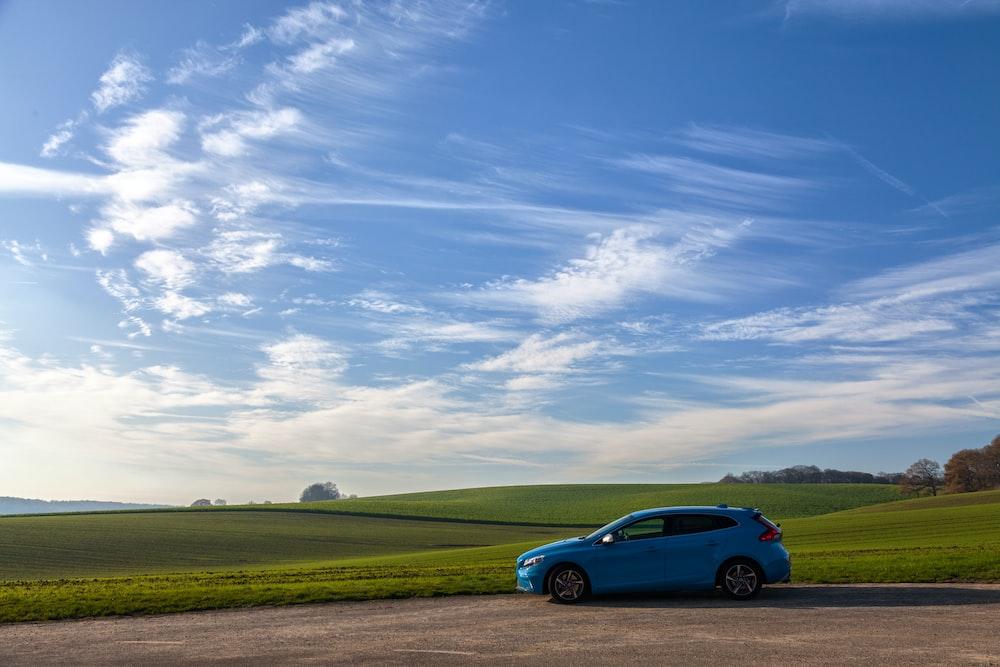 blue 5-door hatchback on asphalt road during daytime