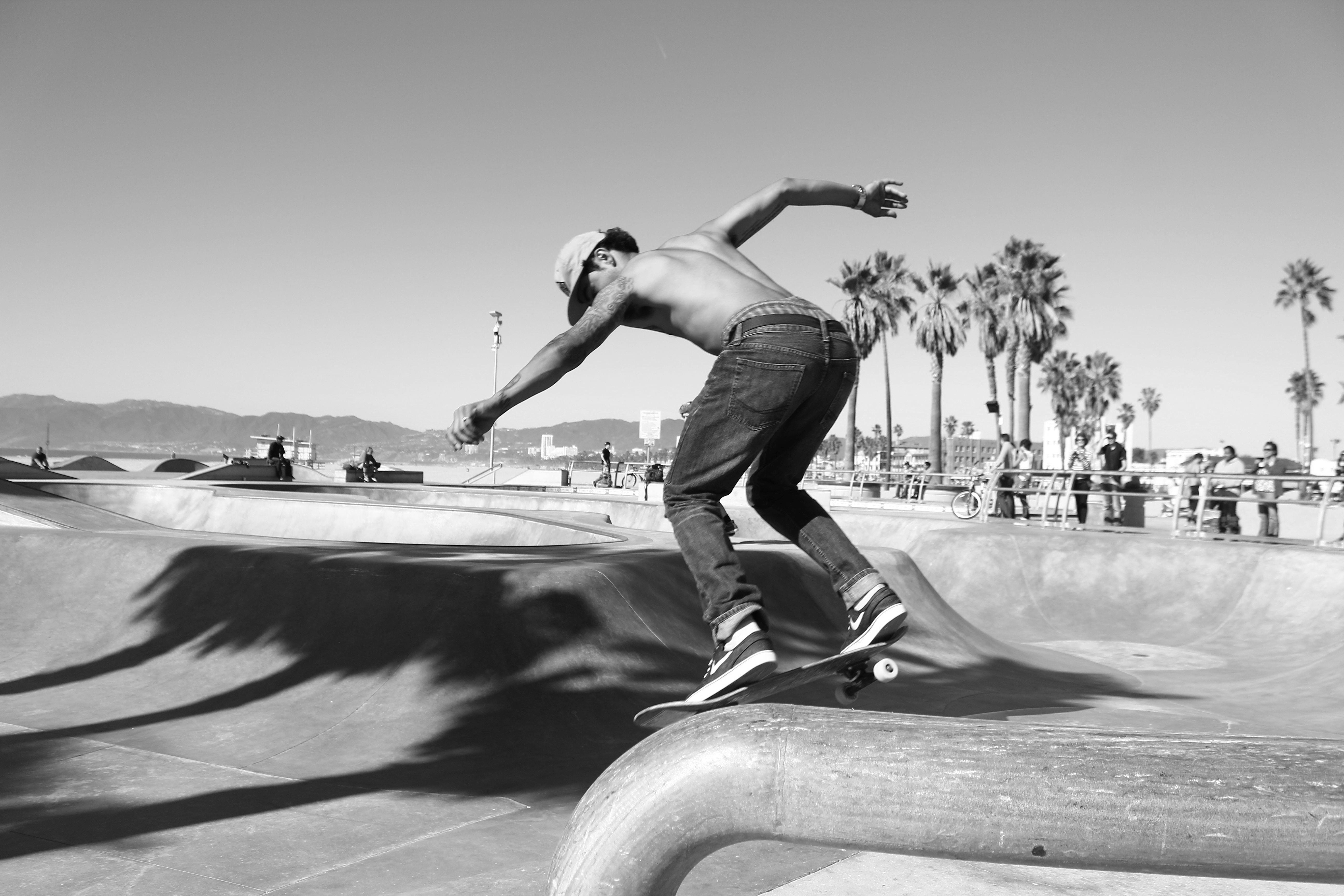 A shirtless man skateboarding at the Venice Beach Skatepark