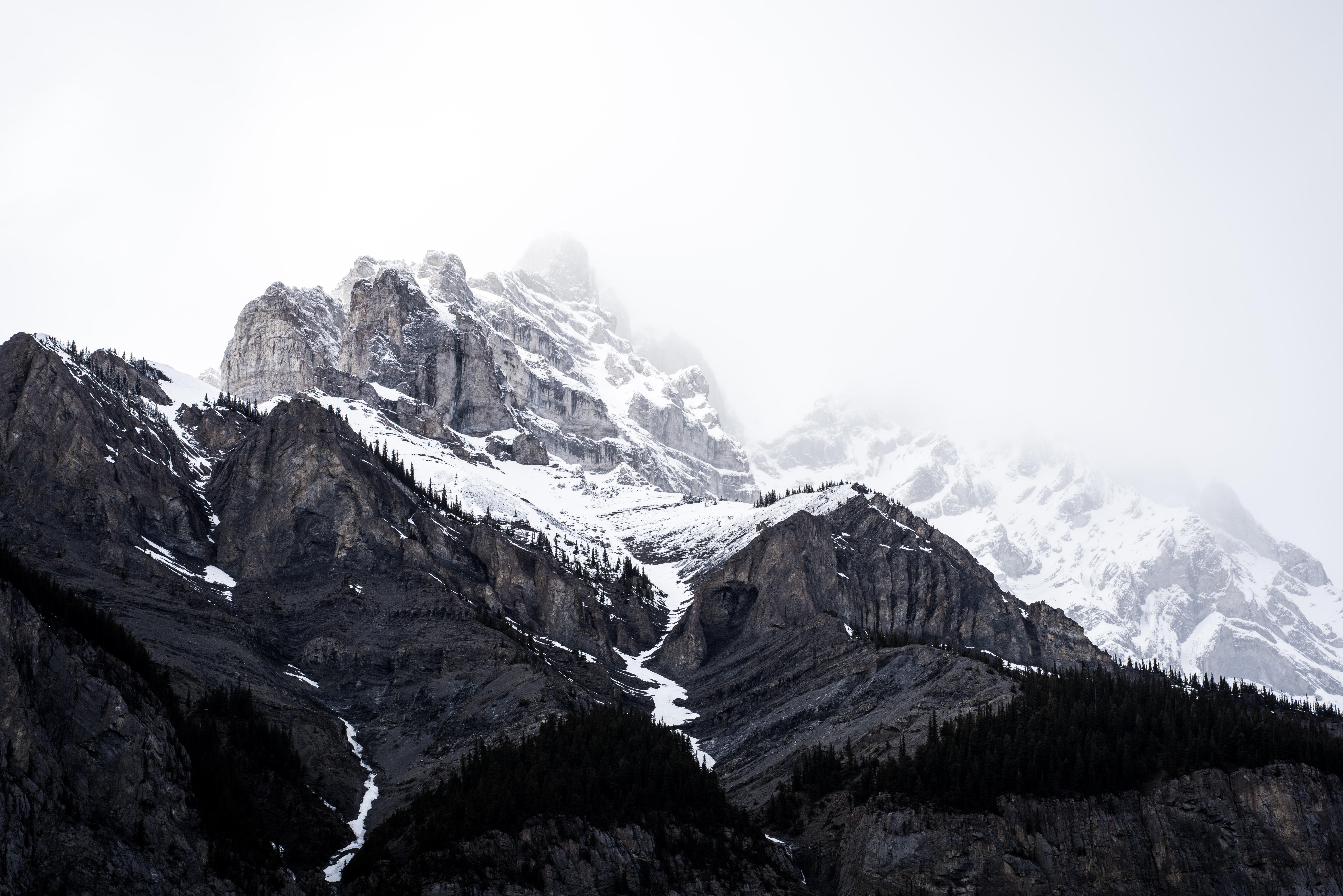 Fog masks the snow capped peaks of Banff