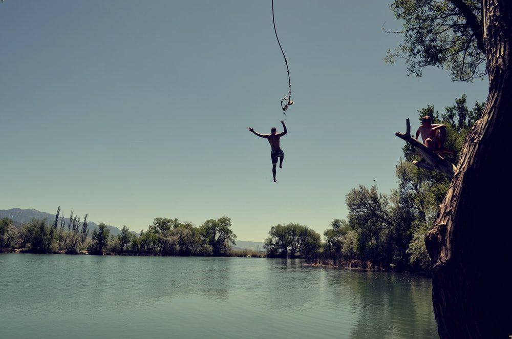 man jumping on body of water with rope