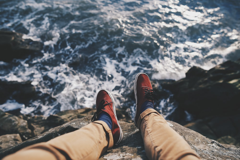 man in red sneakers sitting in cliff near body of water