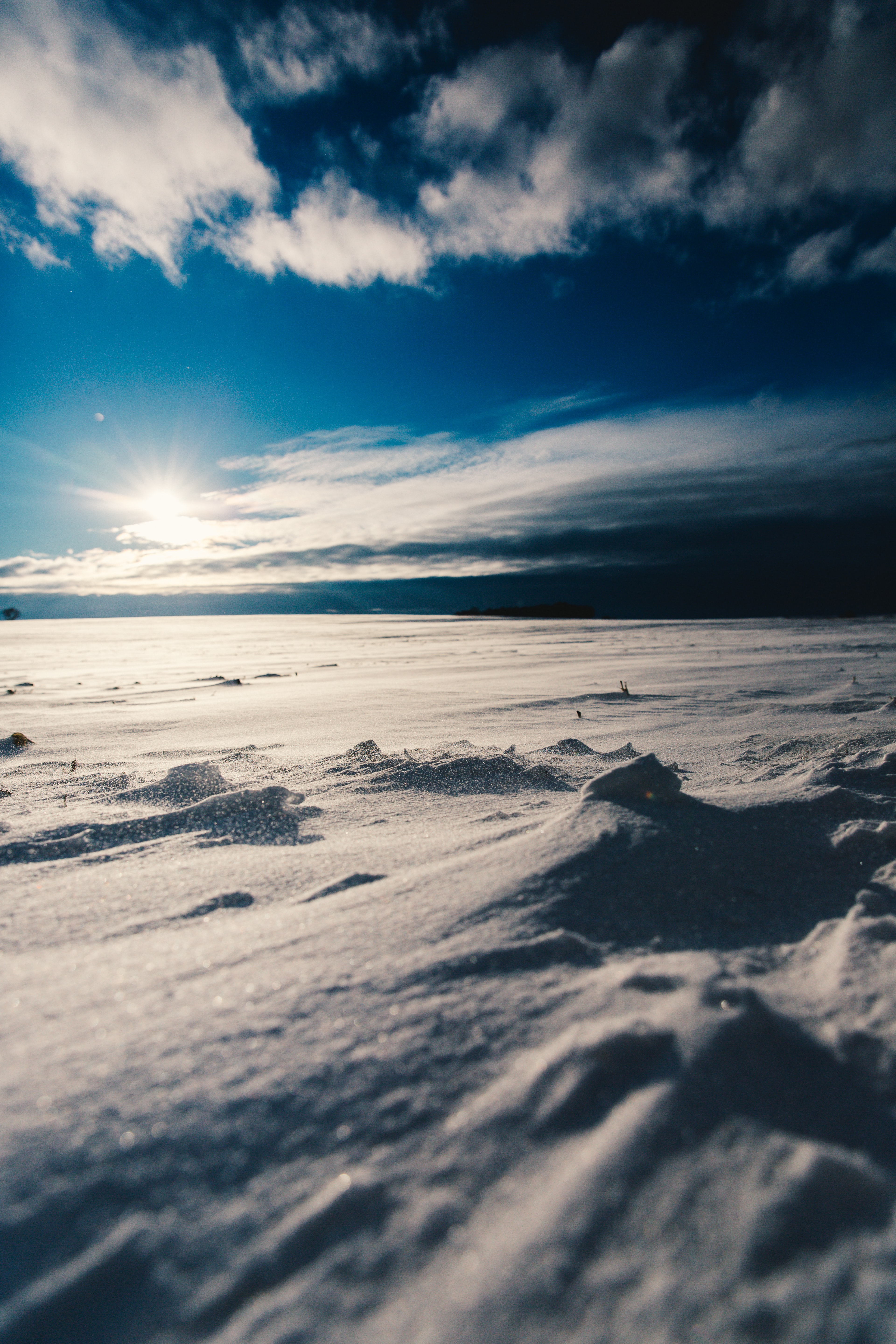 A blue sky in white clouds with white snow fall on the ground
