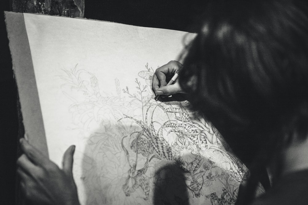 grayscale photo of a woman drawing a flowers