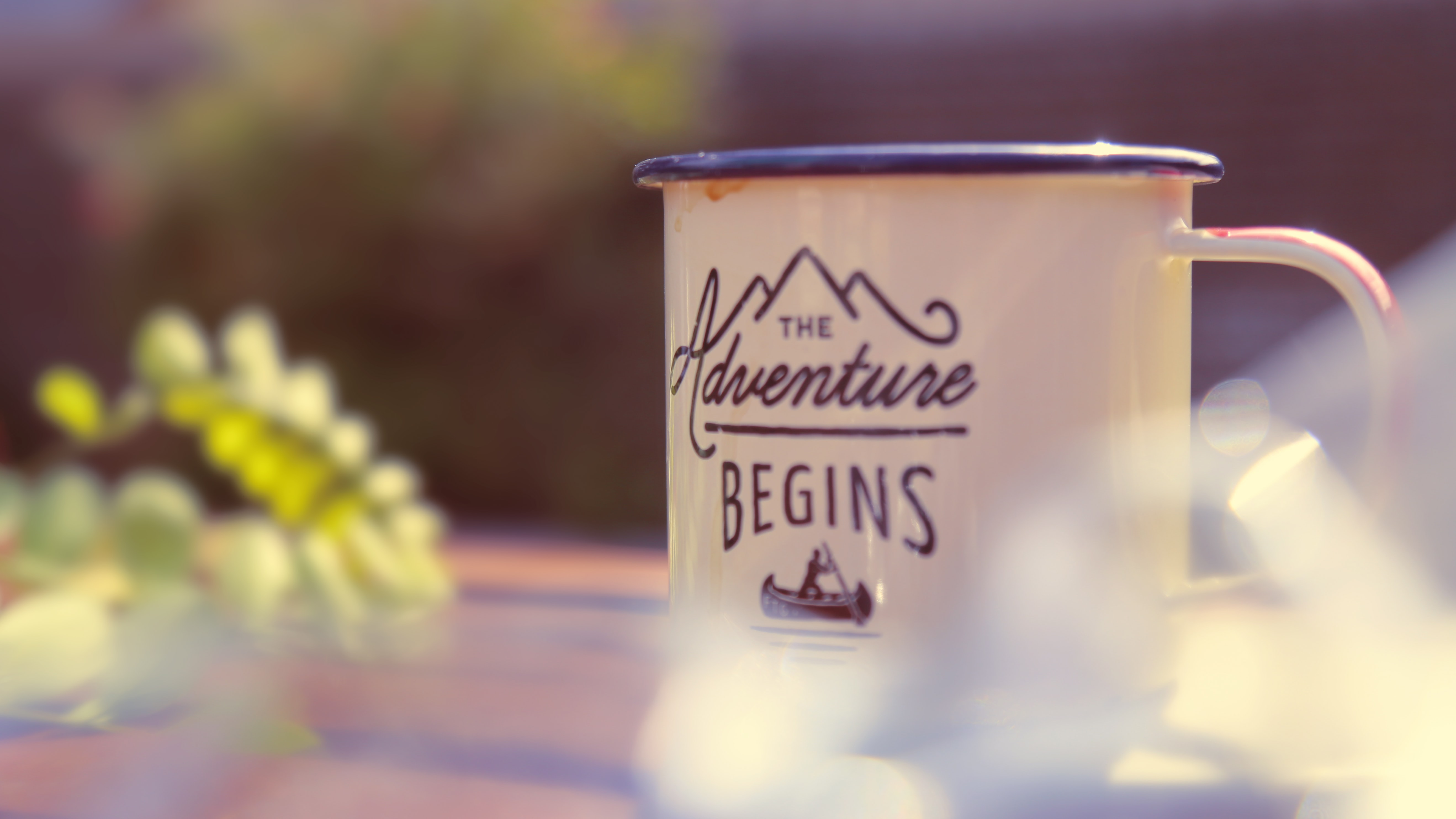 "A macro image of a coffee cup that says ""The Adventure Begins."""