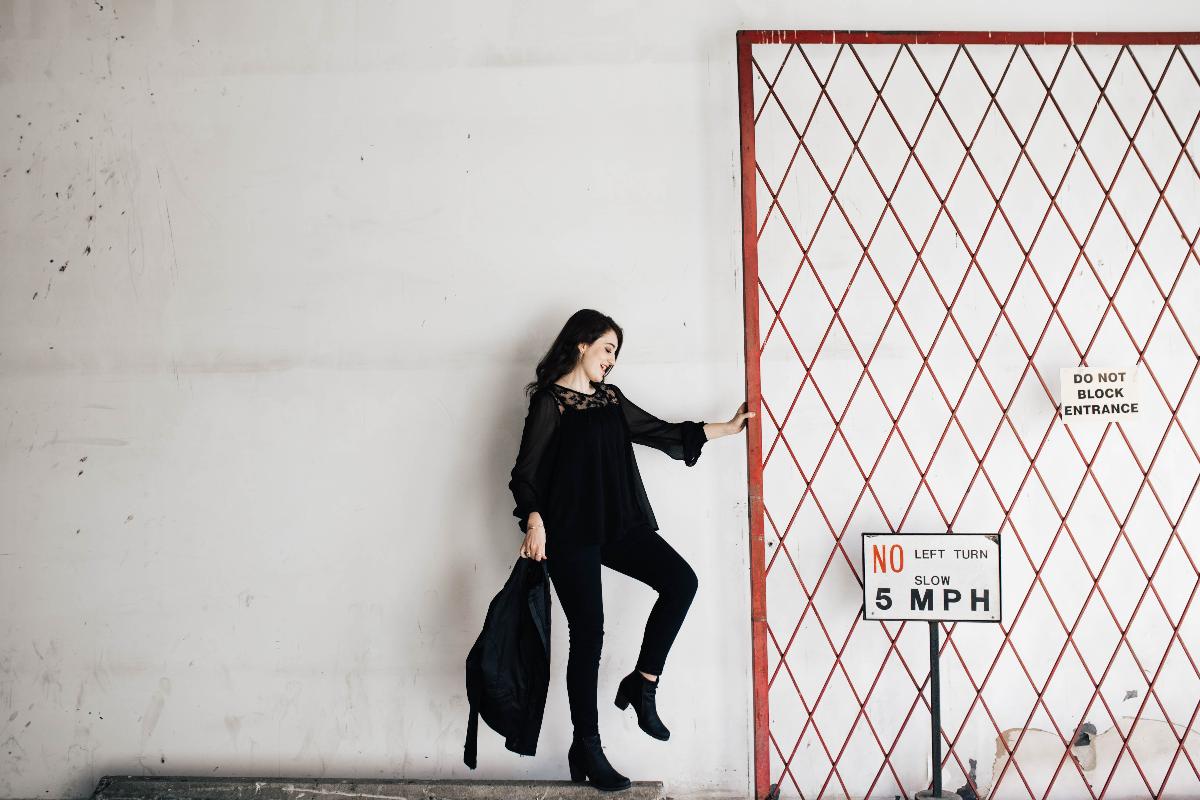 A woman dressed in black is holding onto the entrance gate next to the signs.