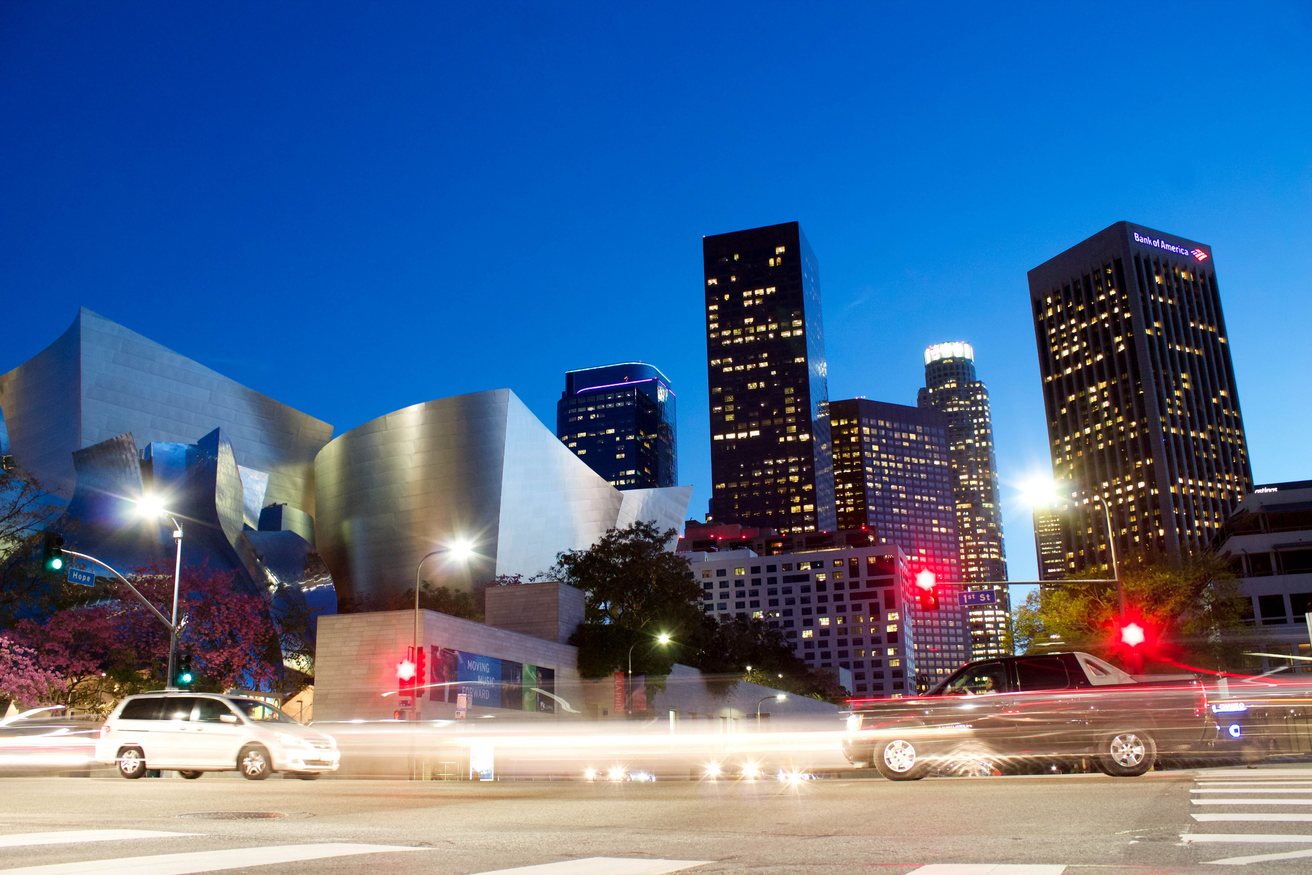 A long-exposure shot of cars in a street of Los Angeles with a modern silver building at the back