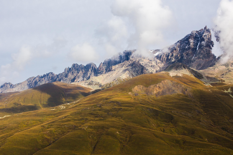 Smoke billows around a rocky mountain ridge by rolling hills