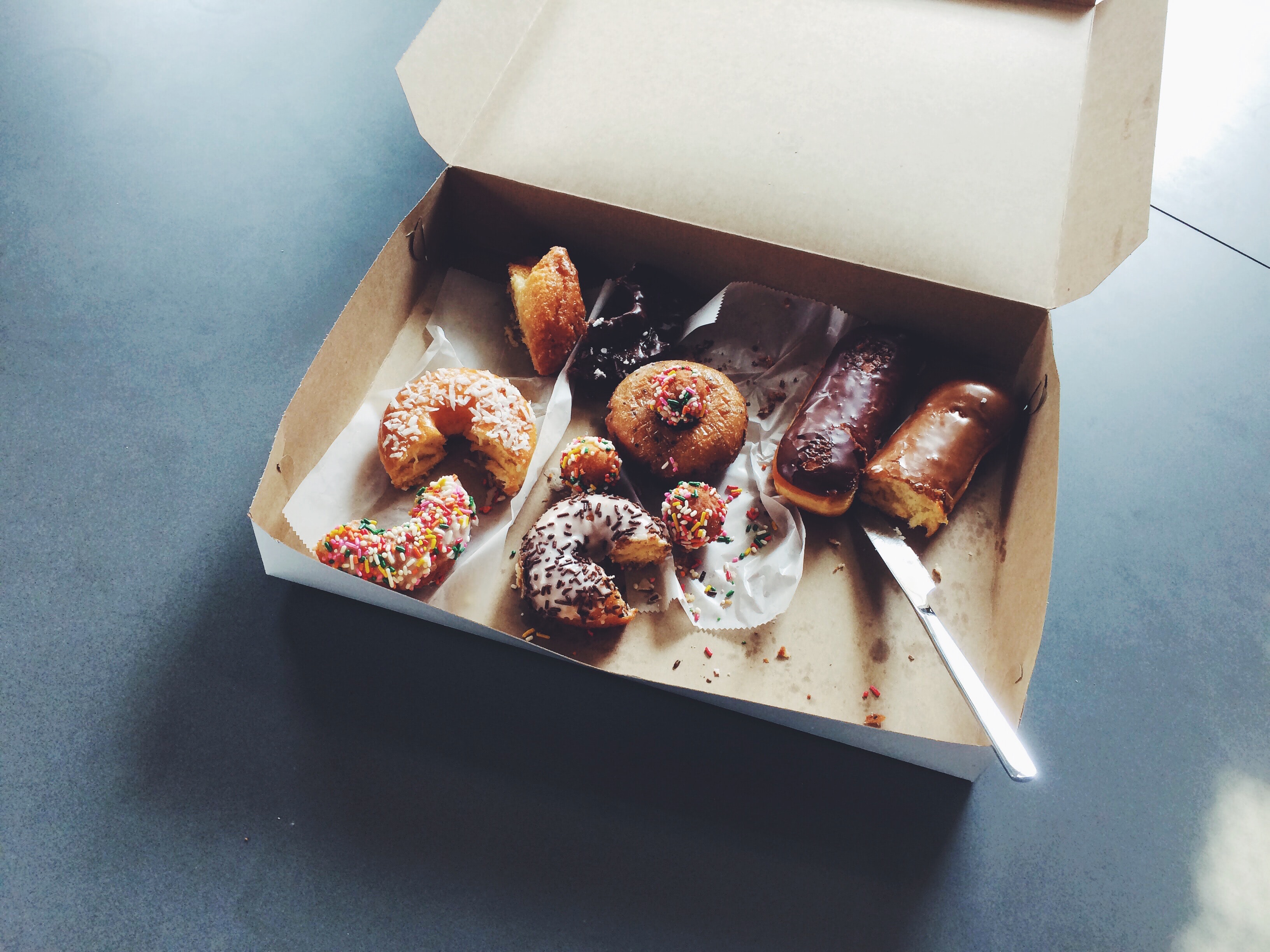 Box of half eaten donuts on an office break room table