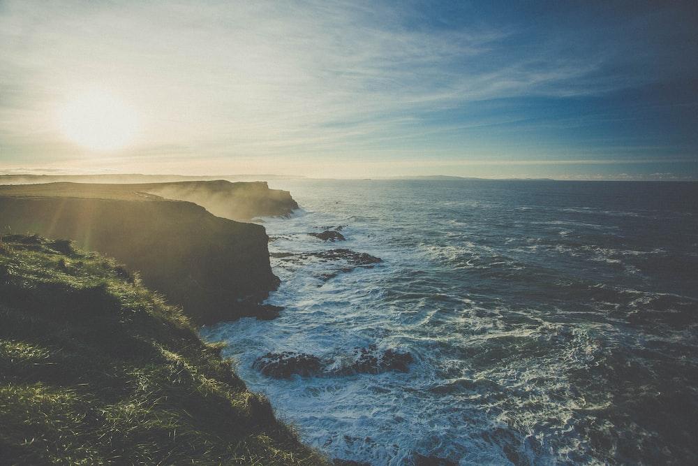 rock cliffs facing rippling body of water
