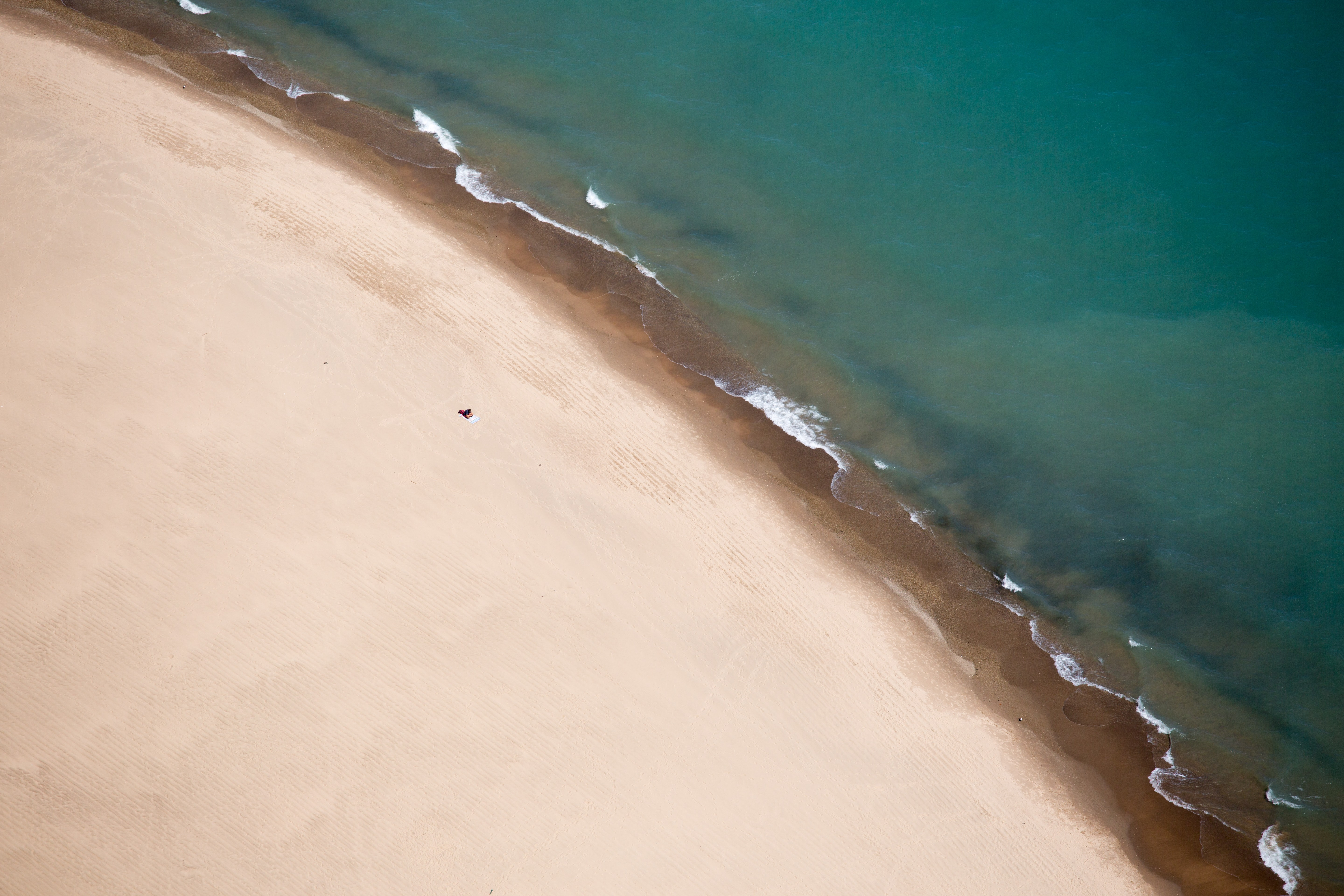 Drone aerial view of a clear water washing on the clean sand shore in Central, Michigan & Delaware