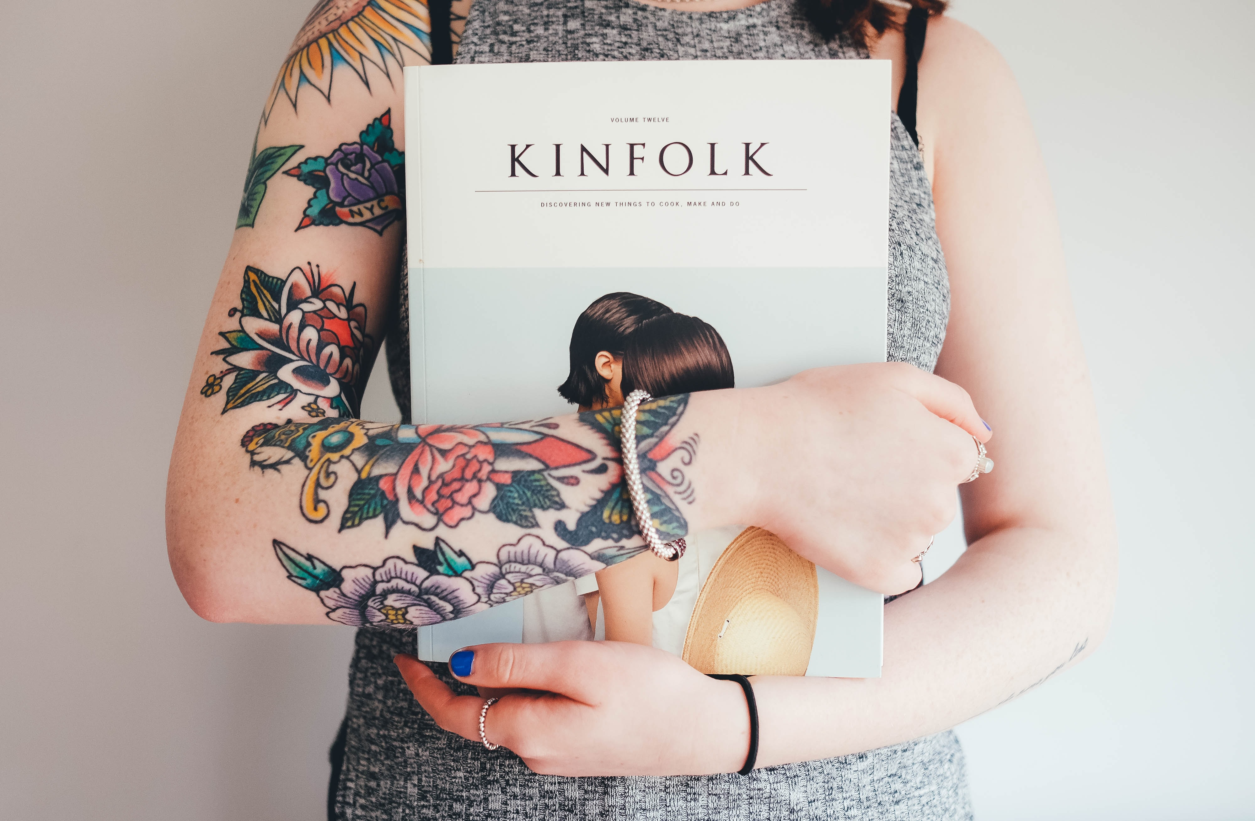 A woman with colorful floral tattoos holding a book in Southampton