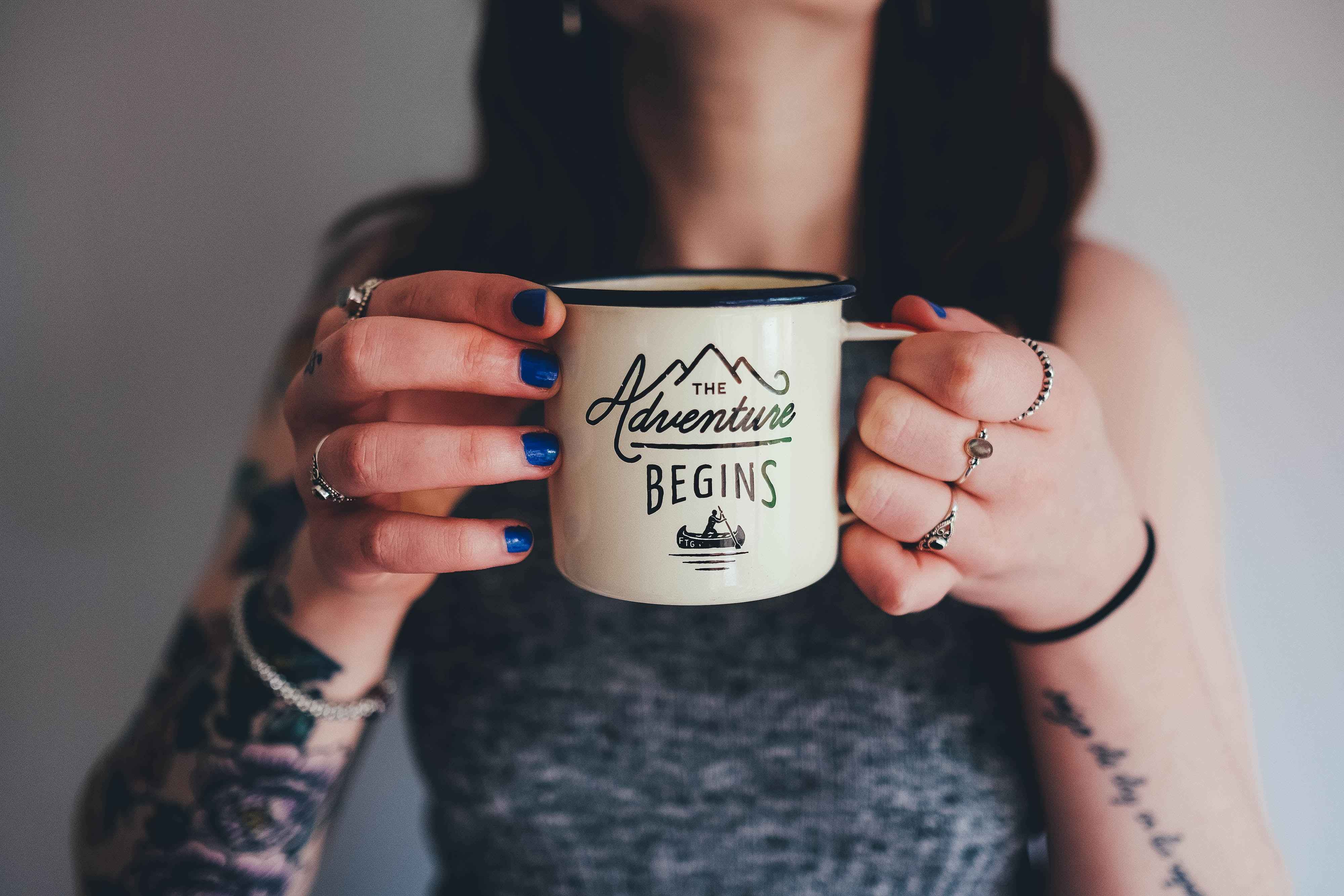 "A woman with tattooed arms holding an enamel cup with ""the adventure begins"" written on it"