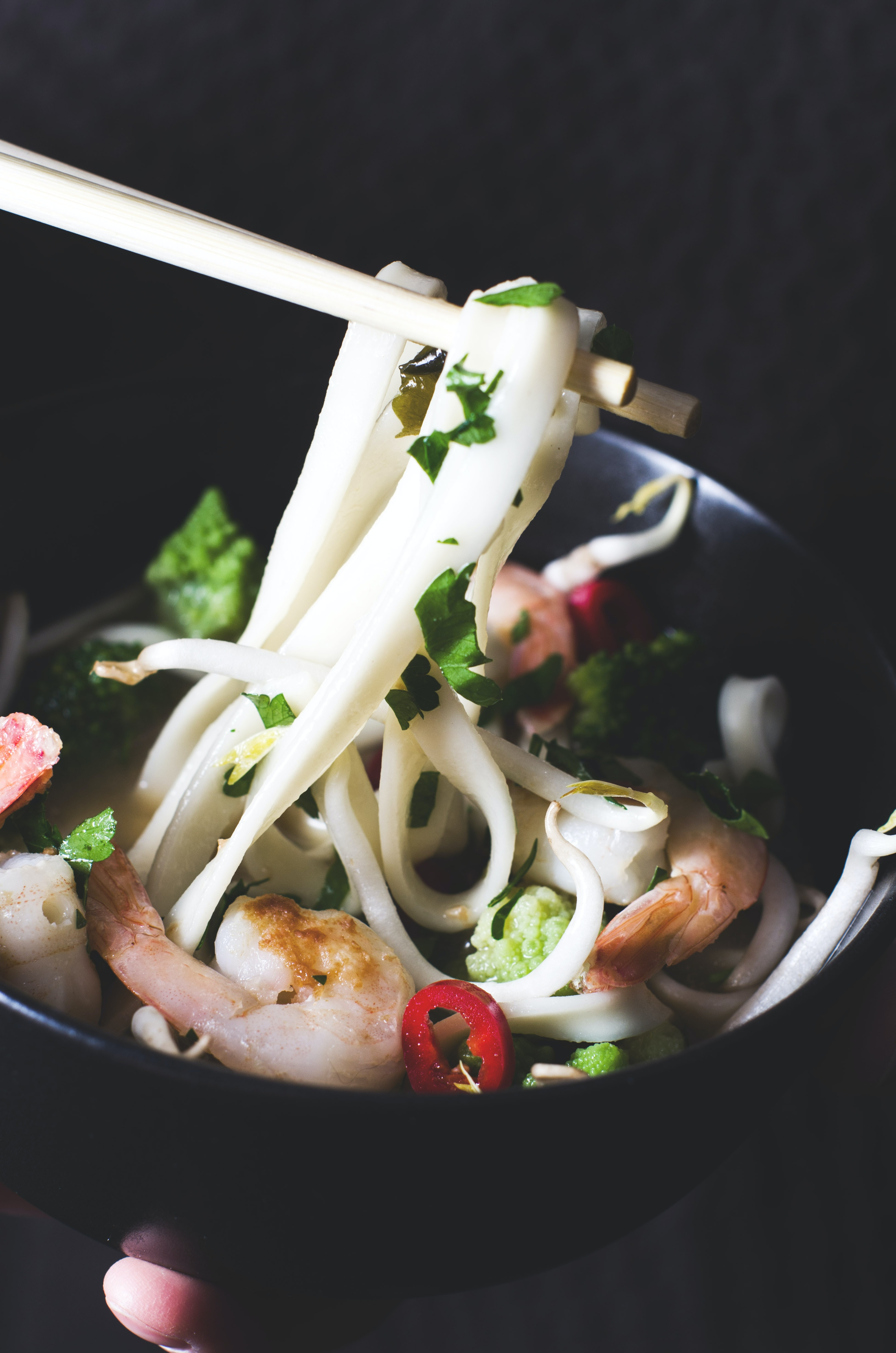 Chopsticks pick up noodles from a bowl full of shrimp and herbs