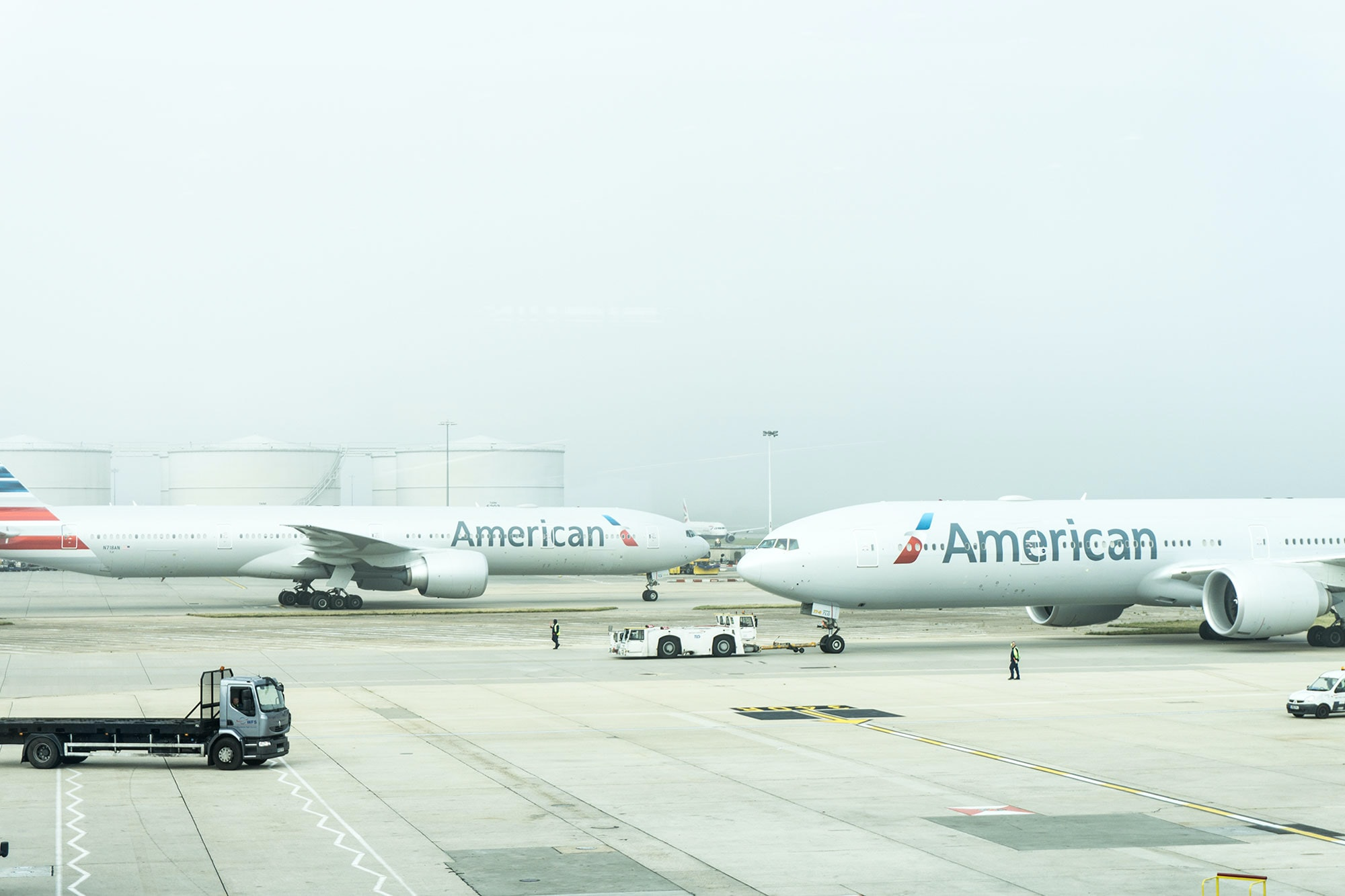 Airport runway with American Airline airplanes and airport vehicles