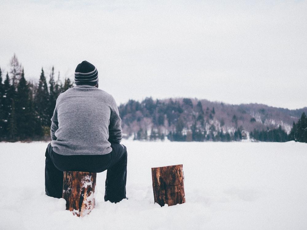 man wearing gray sweater sitting on log during winter