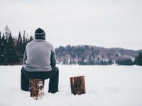 man wearing gray sweater sitting on log during winter