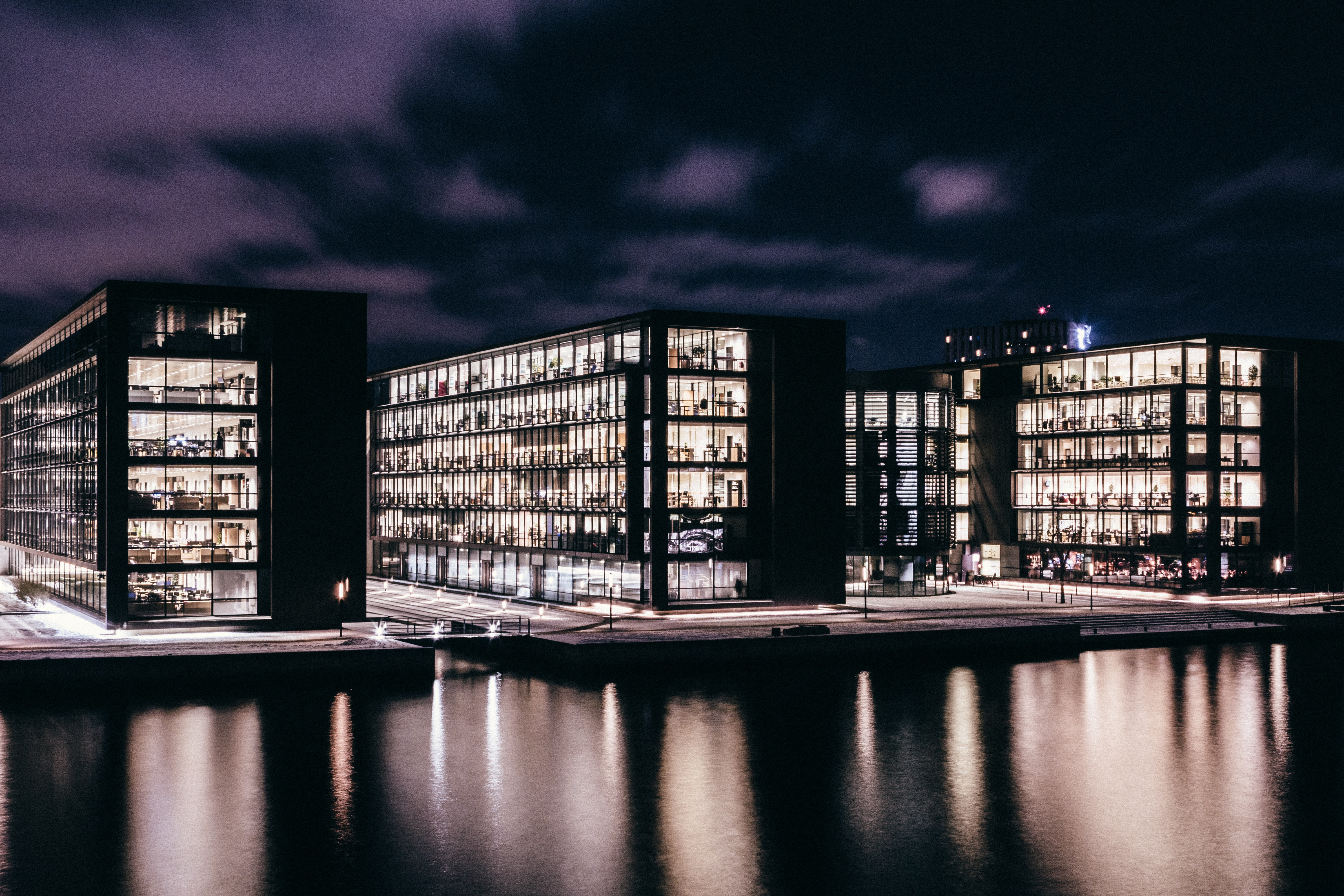three concrete buildings near body of water during nighttime