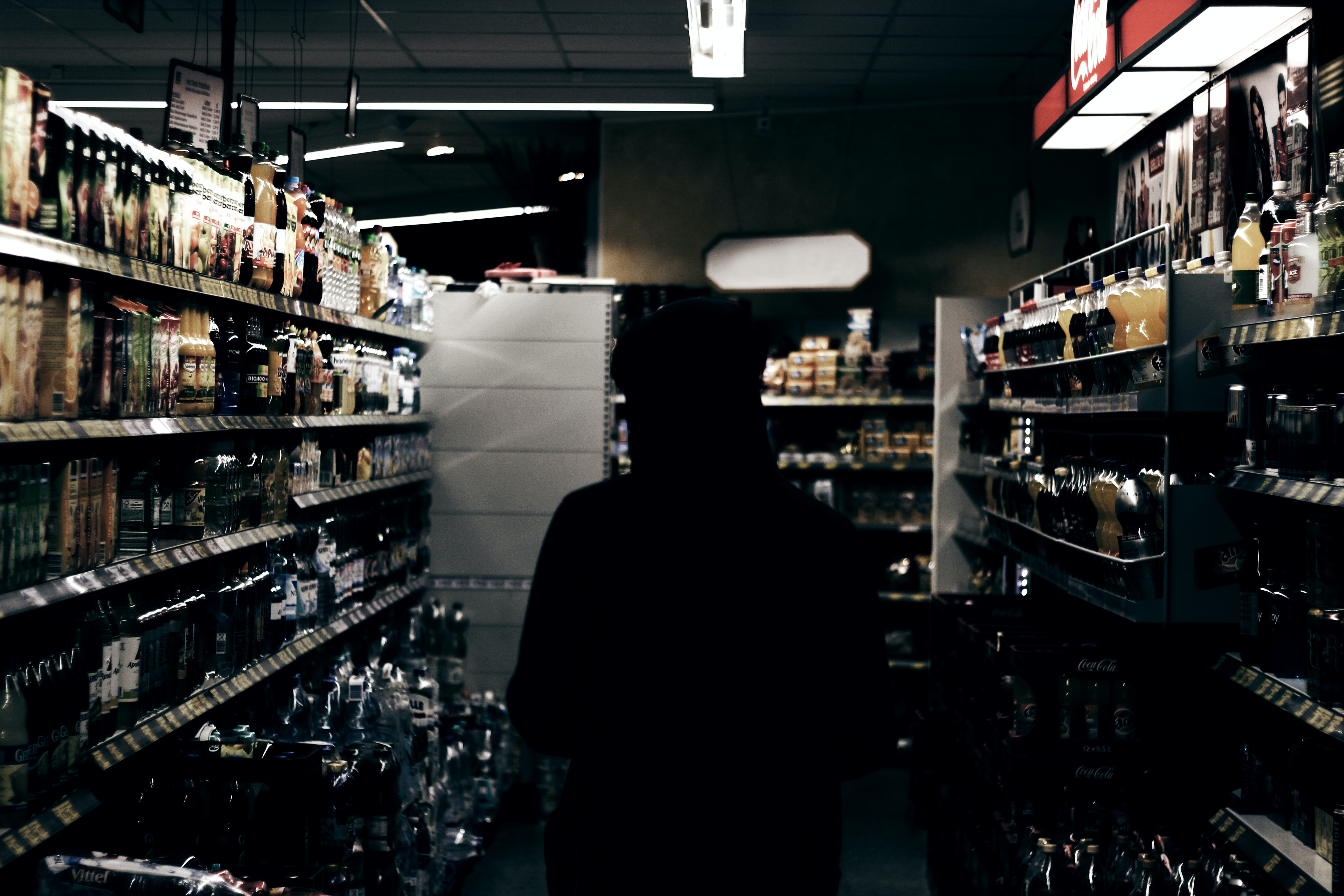 A man wearing black standing in a market next to shelves containing alcohol drinks in silhouette