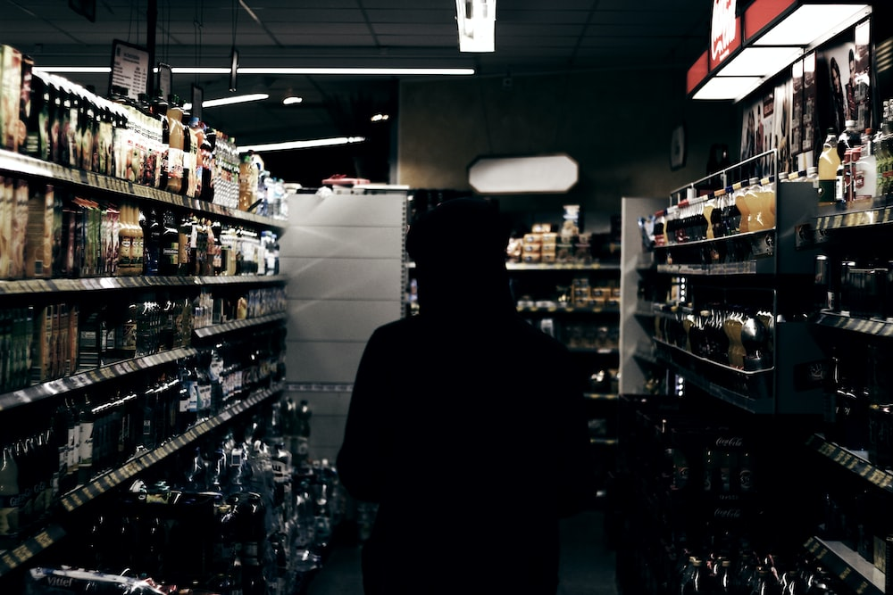 silhouette of person in store liquor section