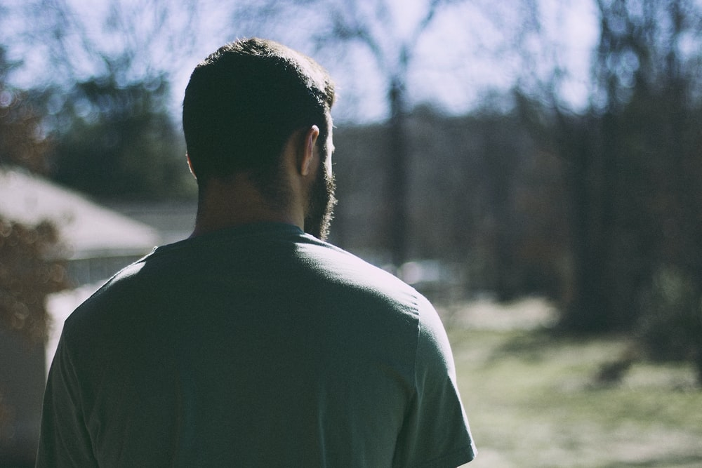 selective focus photography of man staring at woods