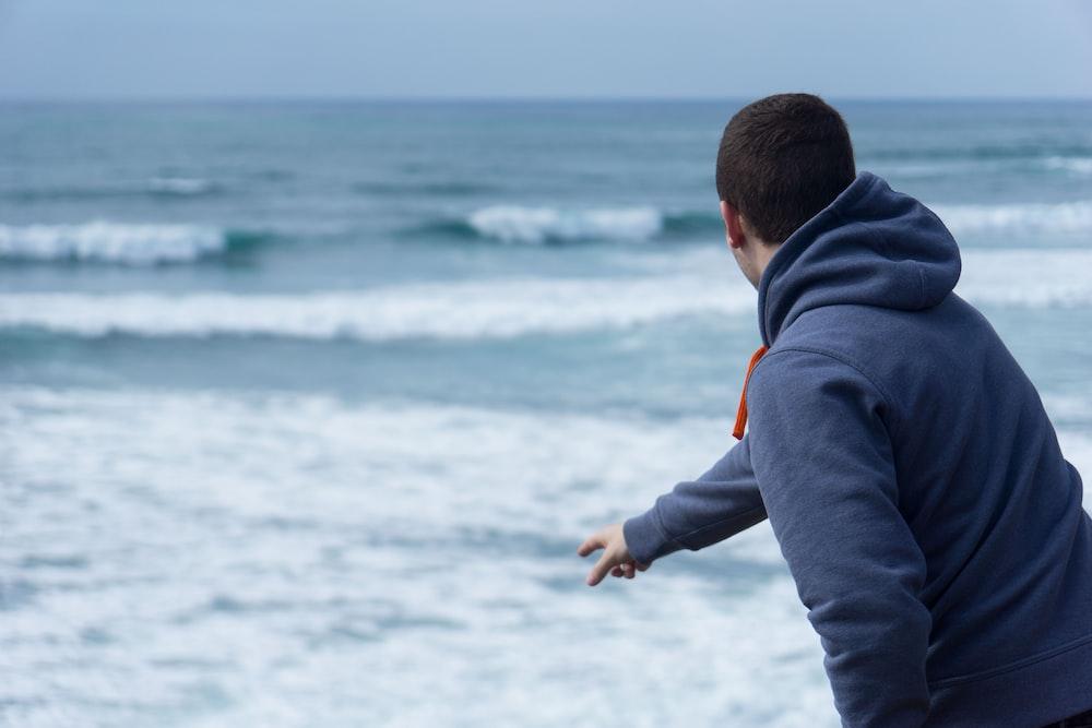 man throw pebble into the beach water