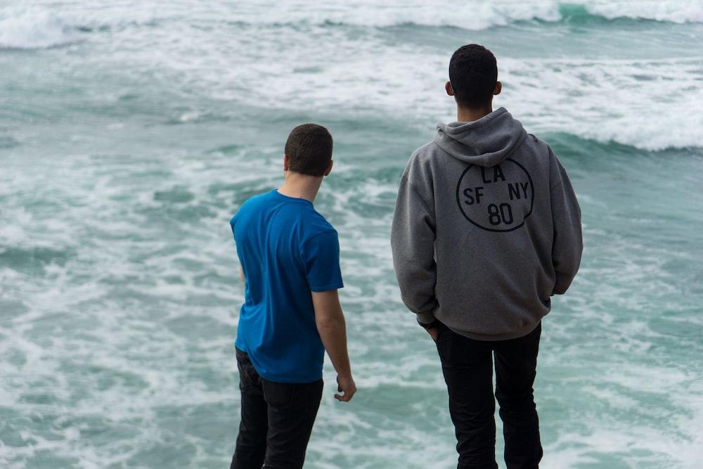 two men standing near body of water