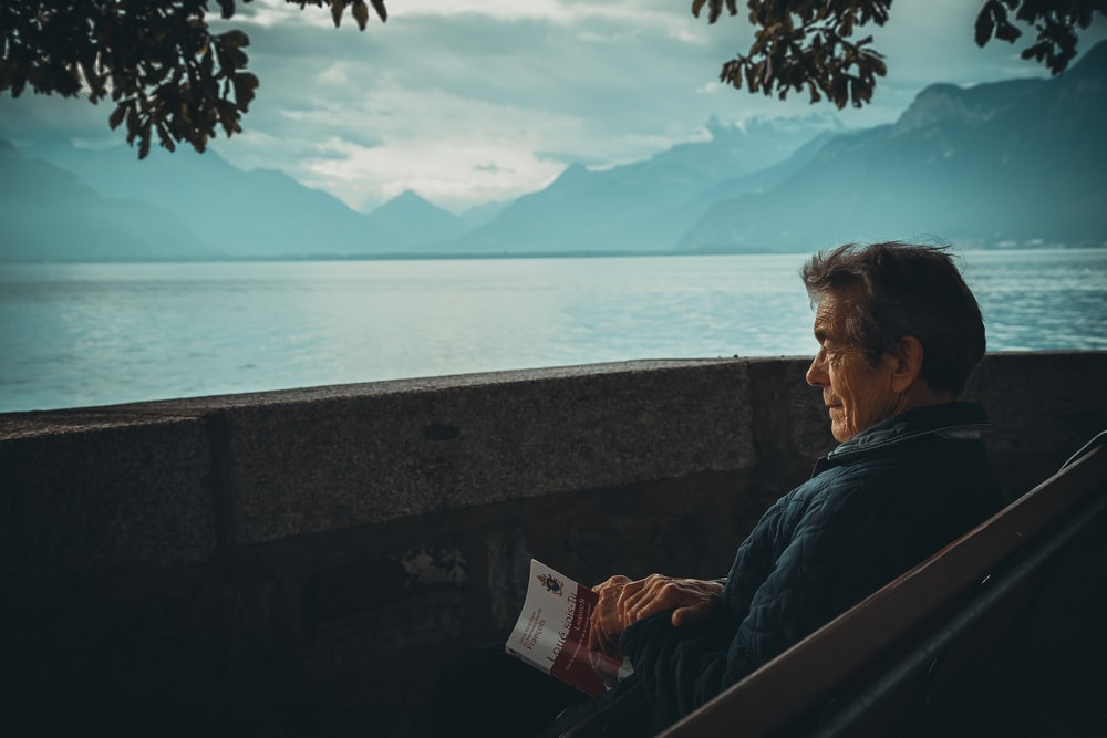 man sitting while holding a book watching on body of water