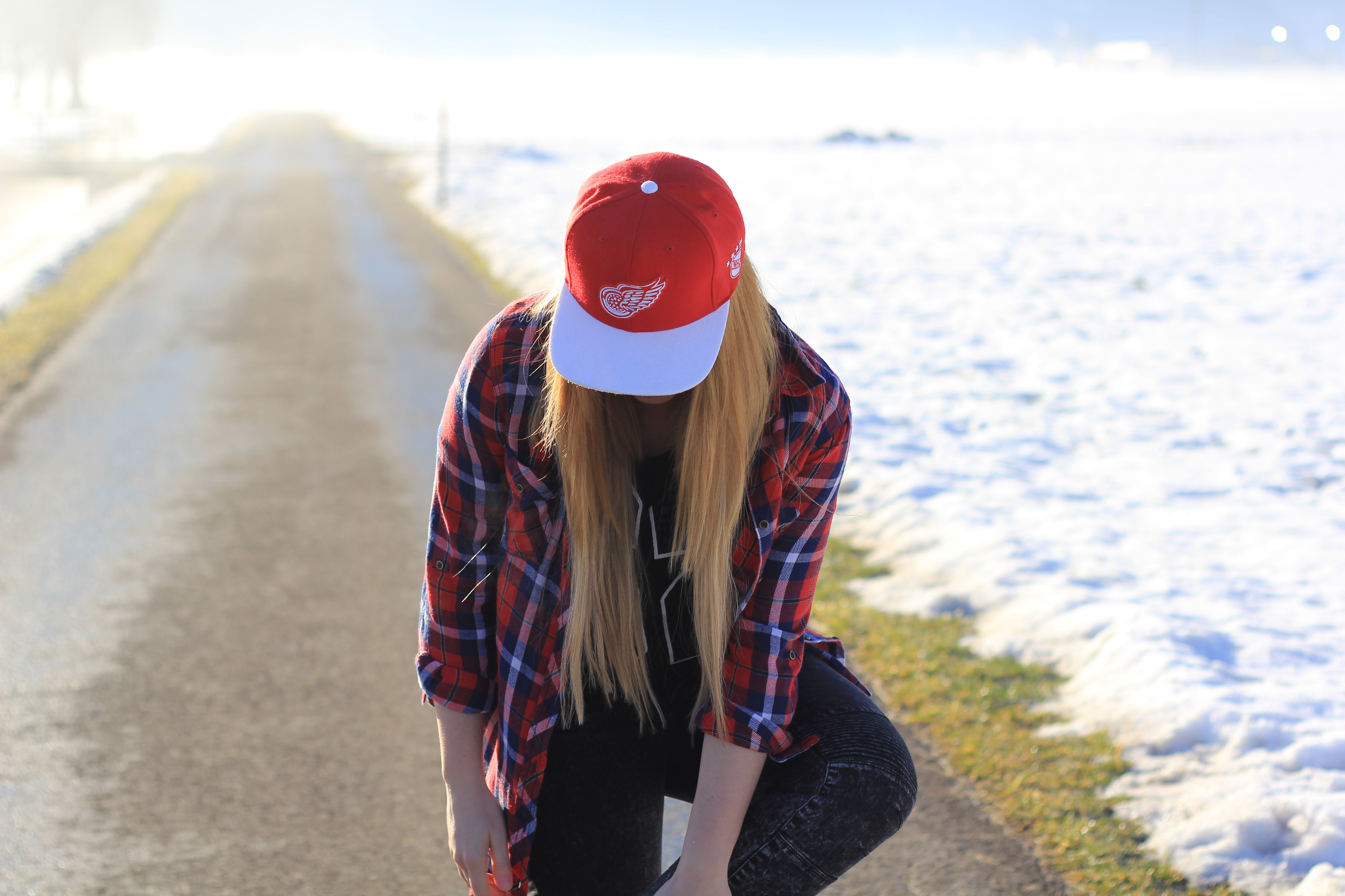 A woman in a plaid shirt and baseball cap kneels on a path aside snow