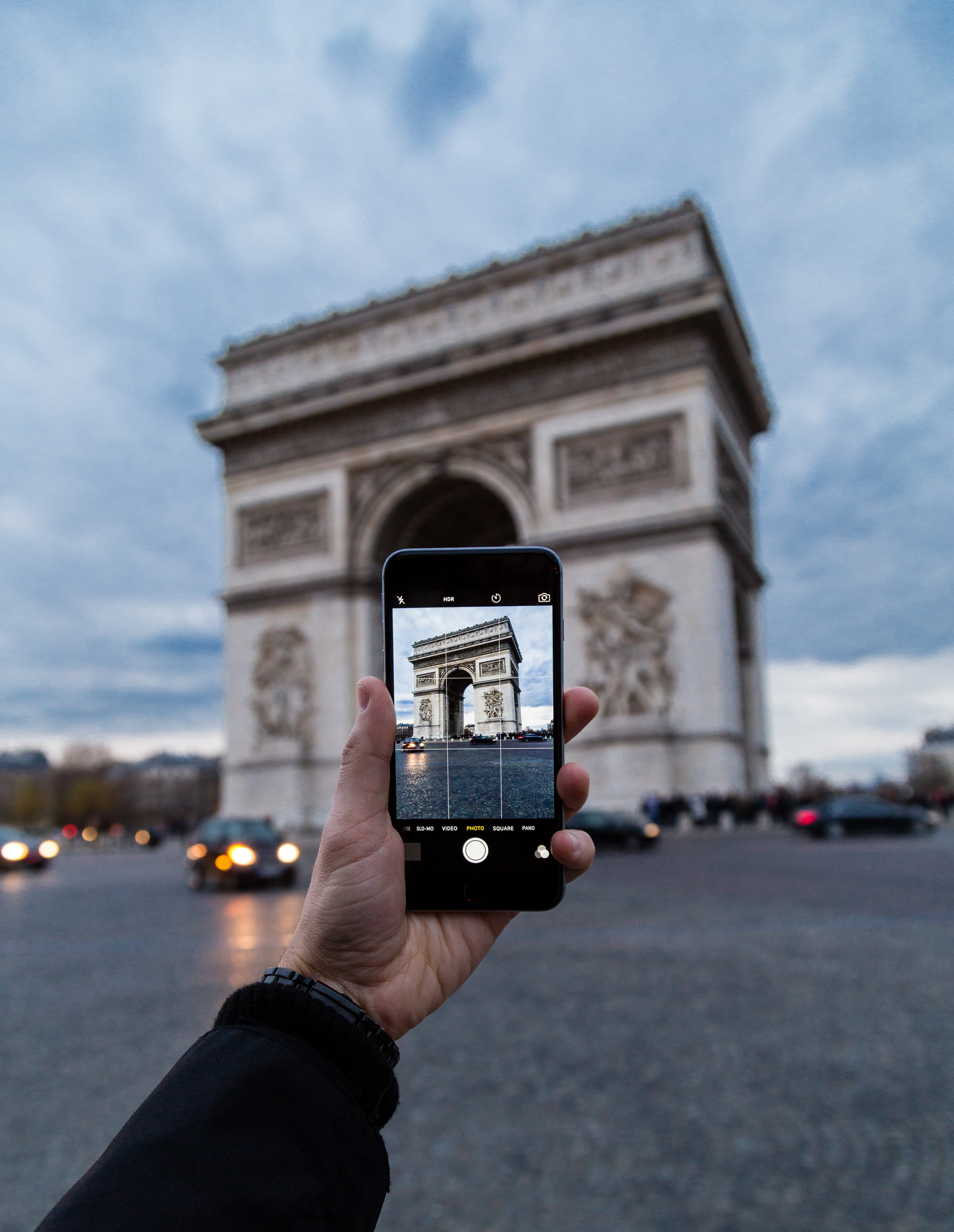 The hand of a man taking a photo of the Arc de Triomphe with his iPhone mobile smartphone while in traffic.