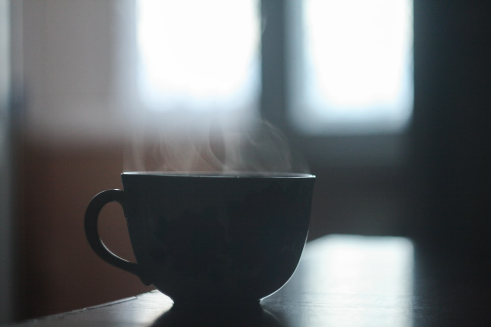 black ceramic teacup on table