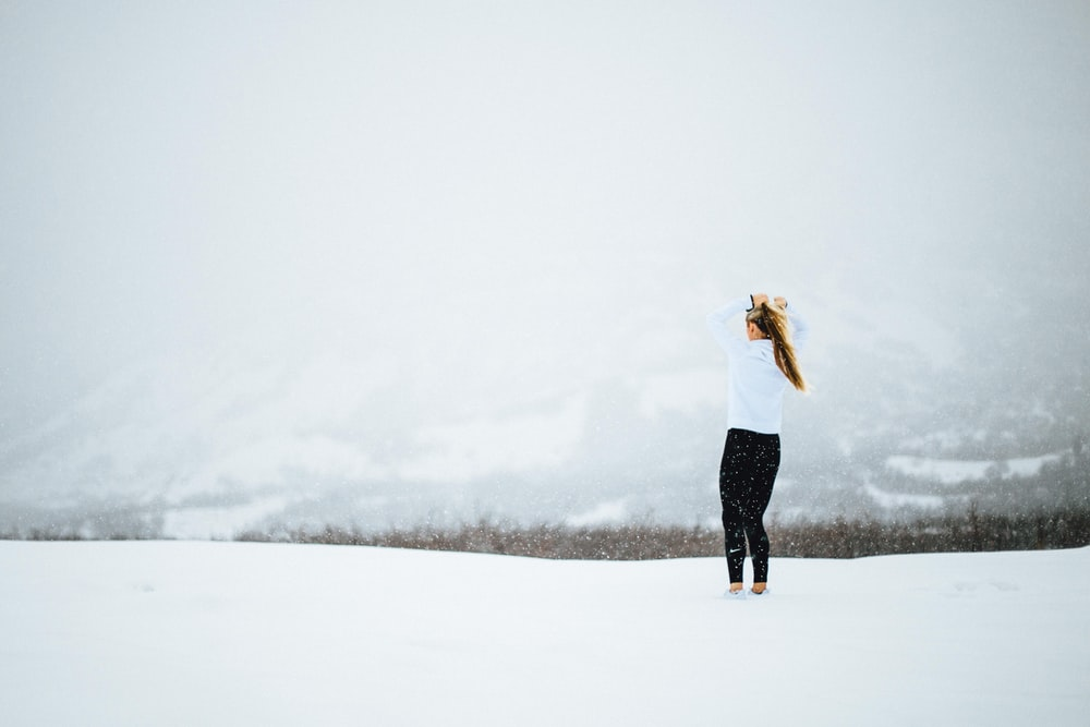 woman standing on open field covered in snow at daytime