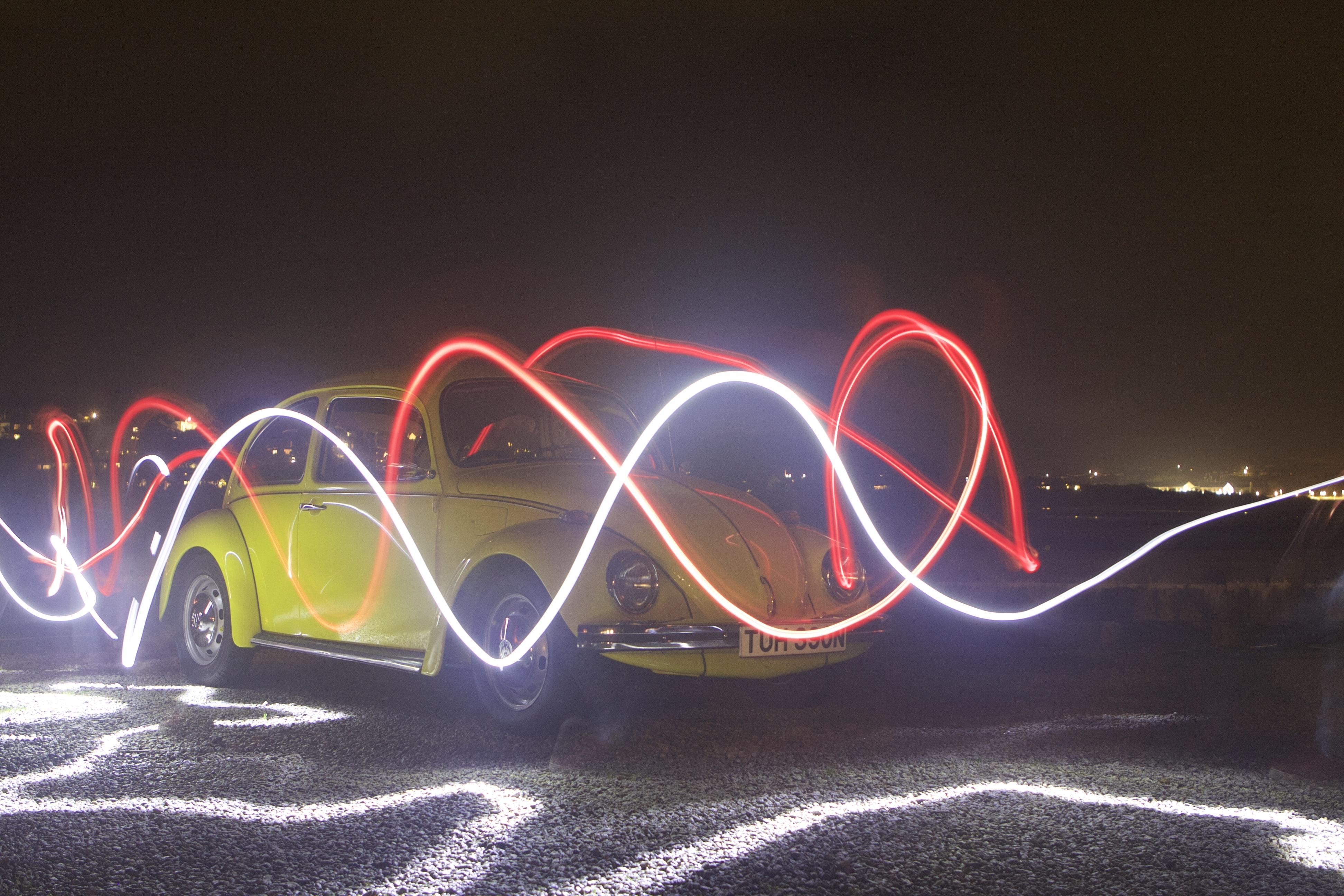 Red and white light trails drawn in the air in front of the yellow vintage Volkswagen beetle at night