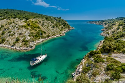 aerial photography of white boat near body of water between green mountain during daytime croatia zoom background