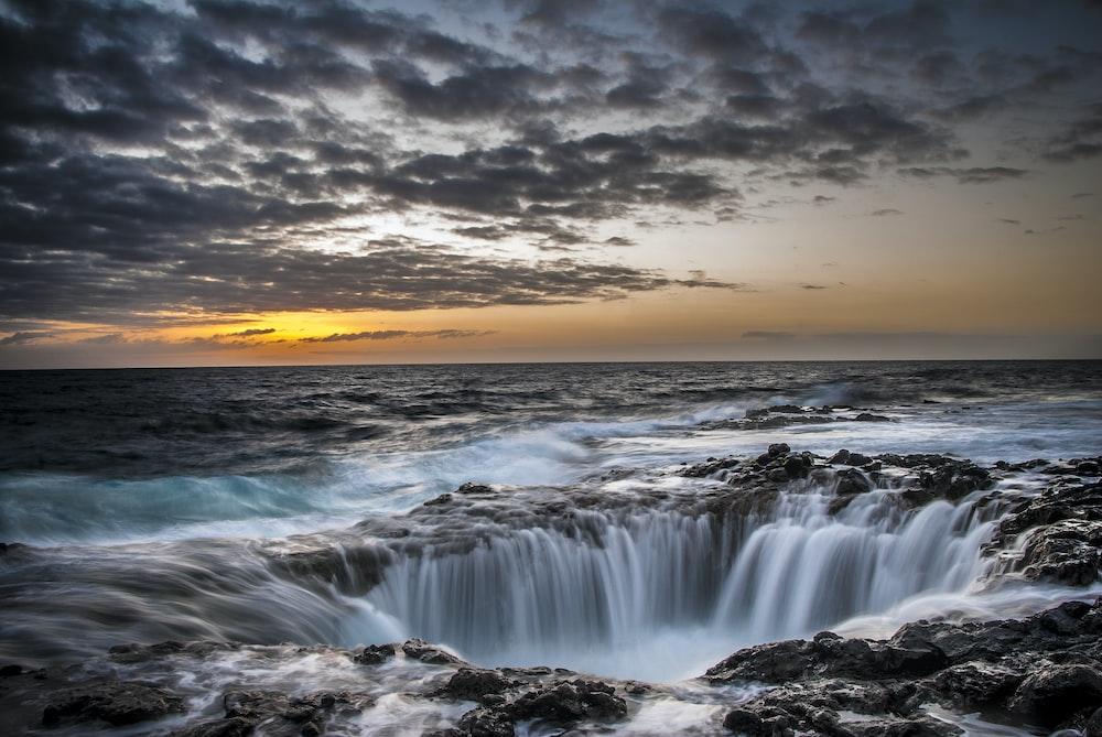 waterfalls under cloudy sky