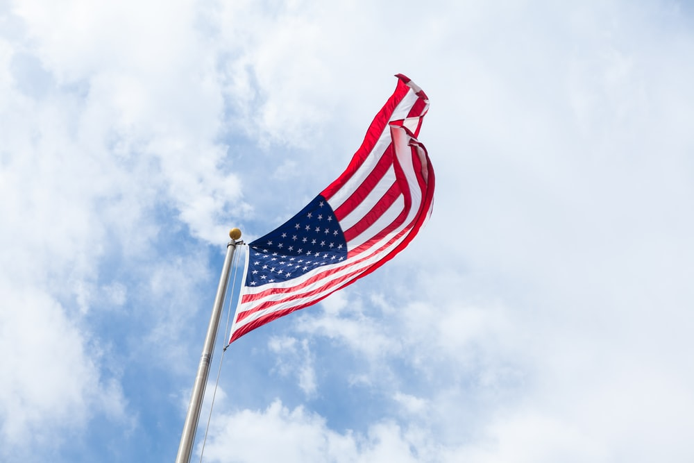 An American flag flies in the wind atop a flagpole