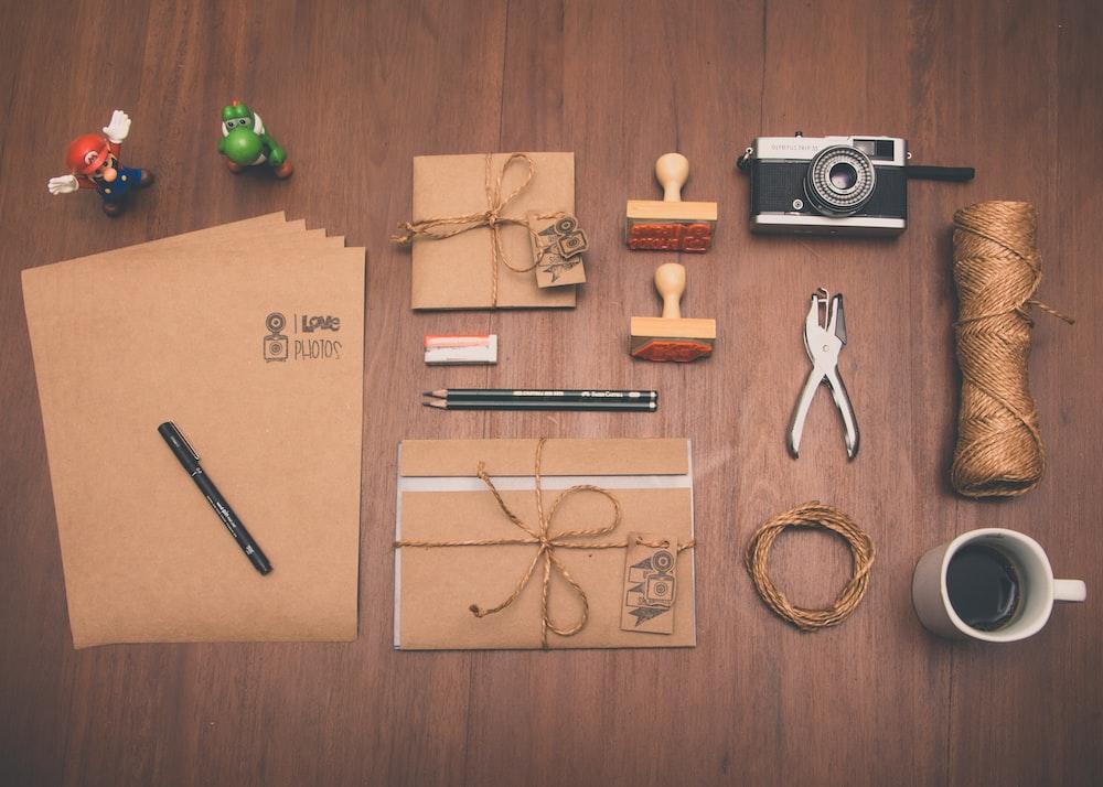 flatlay photograph of brown printer paper, mug, pencil, and camera
